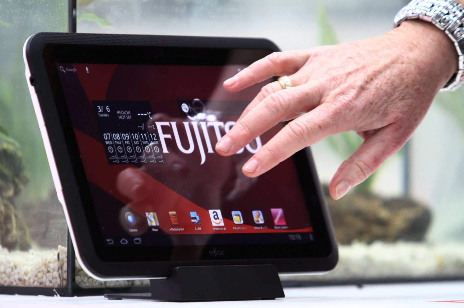 A woman touches a water resistant Fujitsu tablet PC at the information technology fair CEBIT in Hanover, Germany, March 6, 2012.  (EPA Photo)