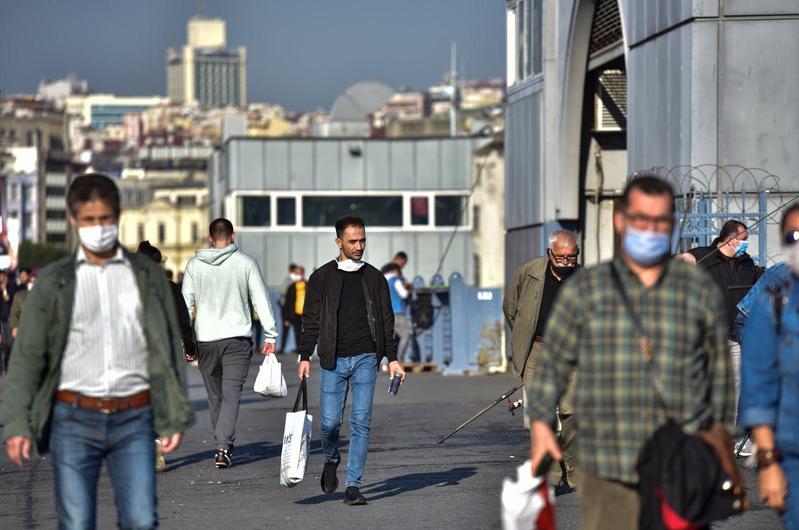 People walk on the Galata Bridge, in Istanbul, Turkey, Nov. 2, 2020. (DHA Photo)