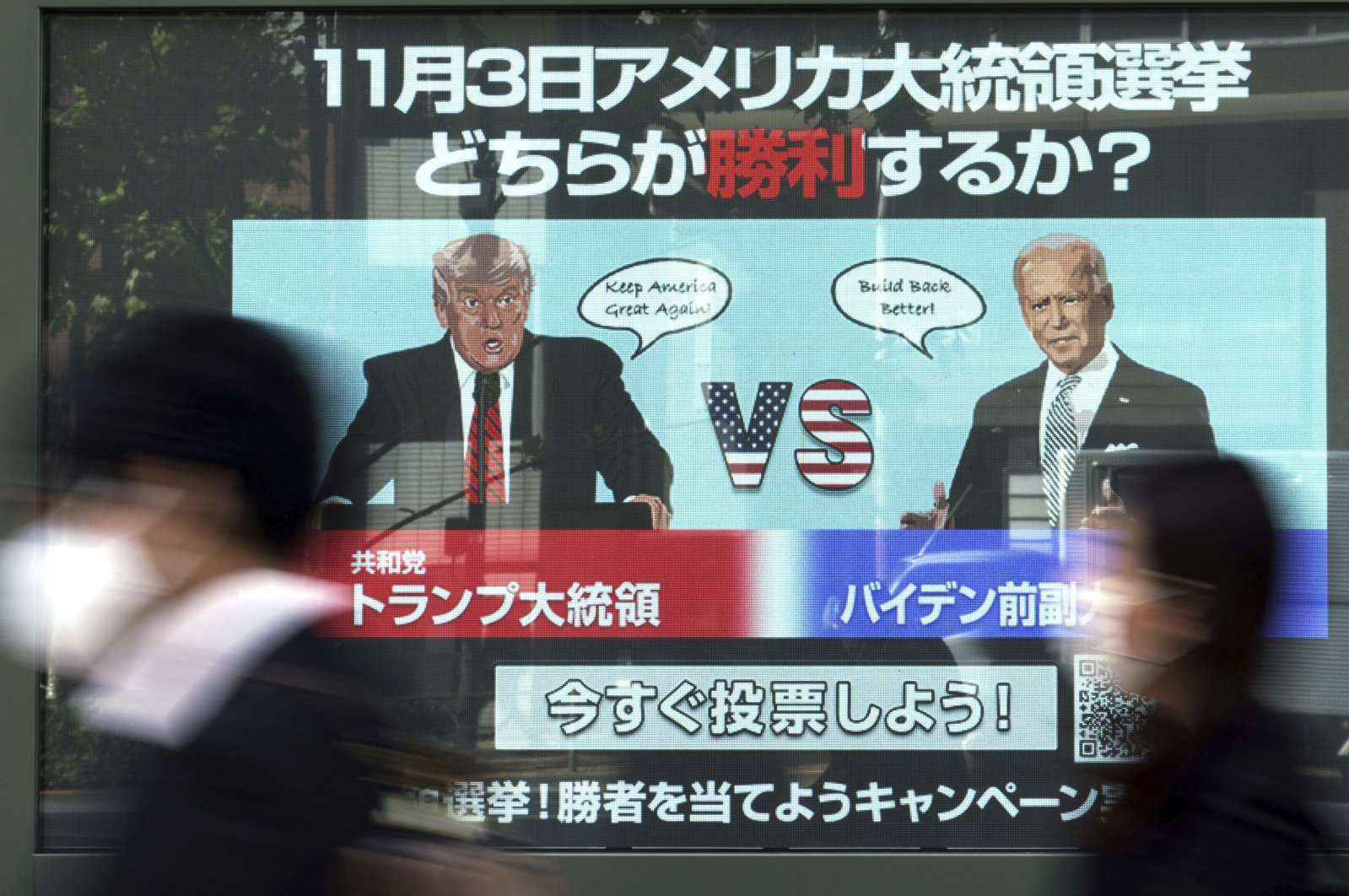 People walk past a screen showing illustrations depicting Donald Trump (L) and Joe Biden for an online vote to predict the winner in the Nov. 3 U.S. presidential election, in Tokyo on Oct. 26, 2020. (AP Photo)