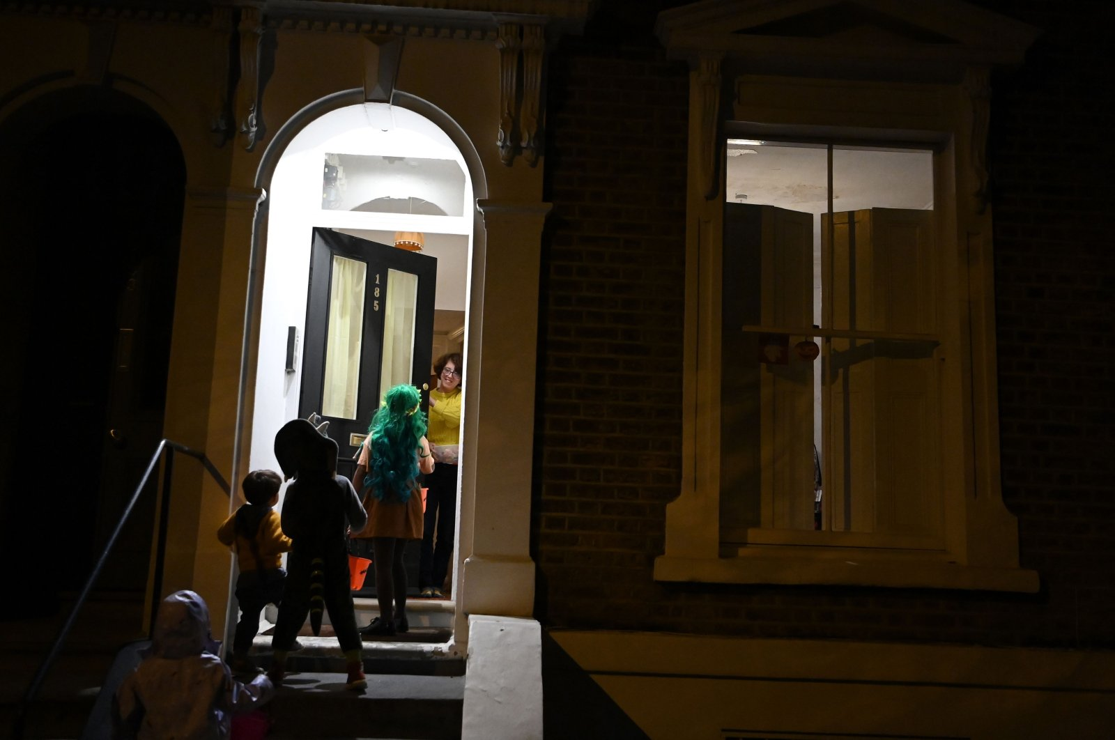 Children knock on a door as they go trick-or-treating for Halloween in east London, Oct. 31, 2020. (AFP Photo)
