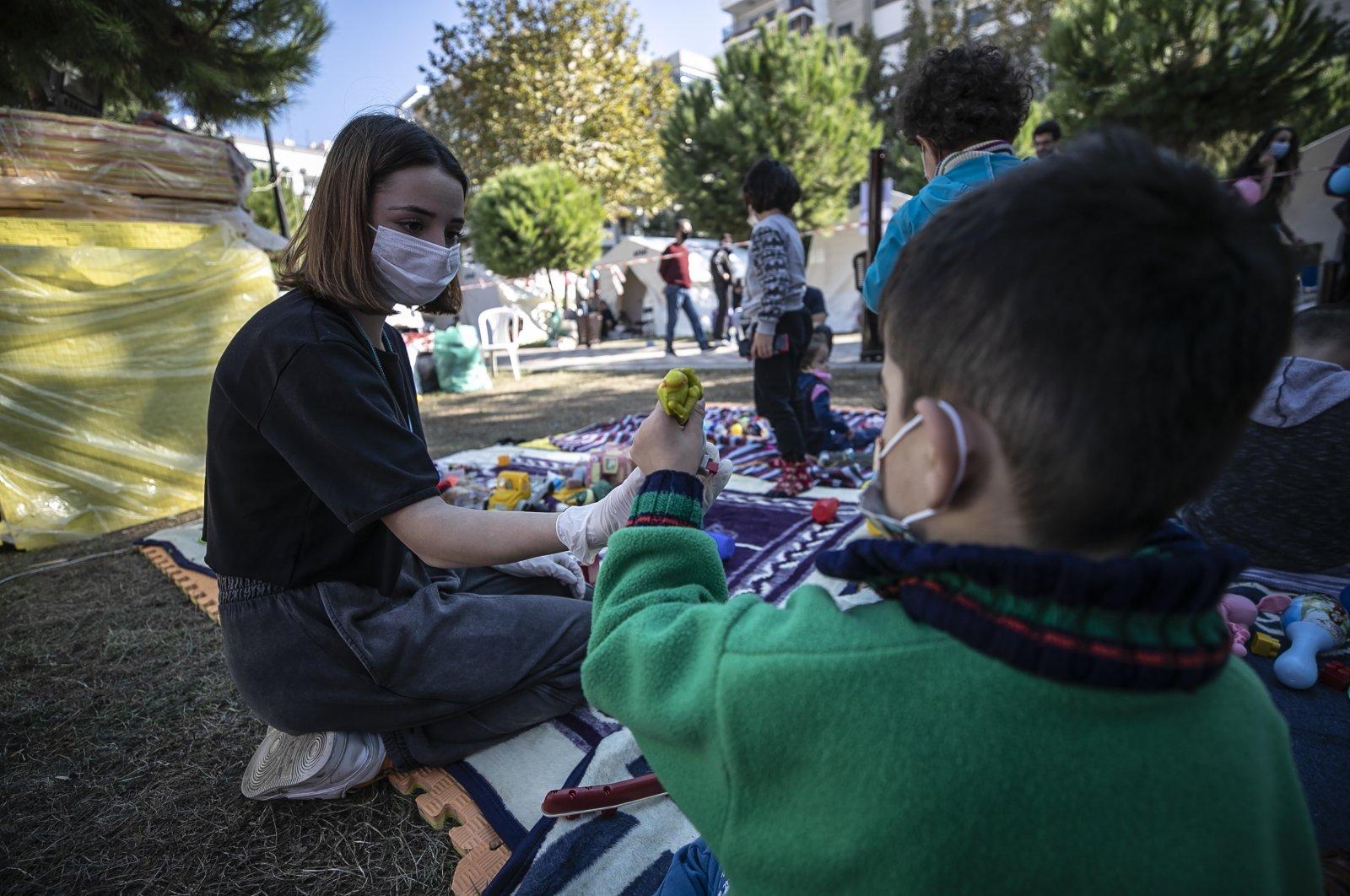 Volunteers play with children at a makeshift activity center in the Bayraklı district, in Izmir, western Turkey, Nov. 4, 2020. (AA Photo)