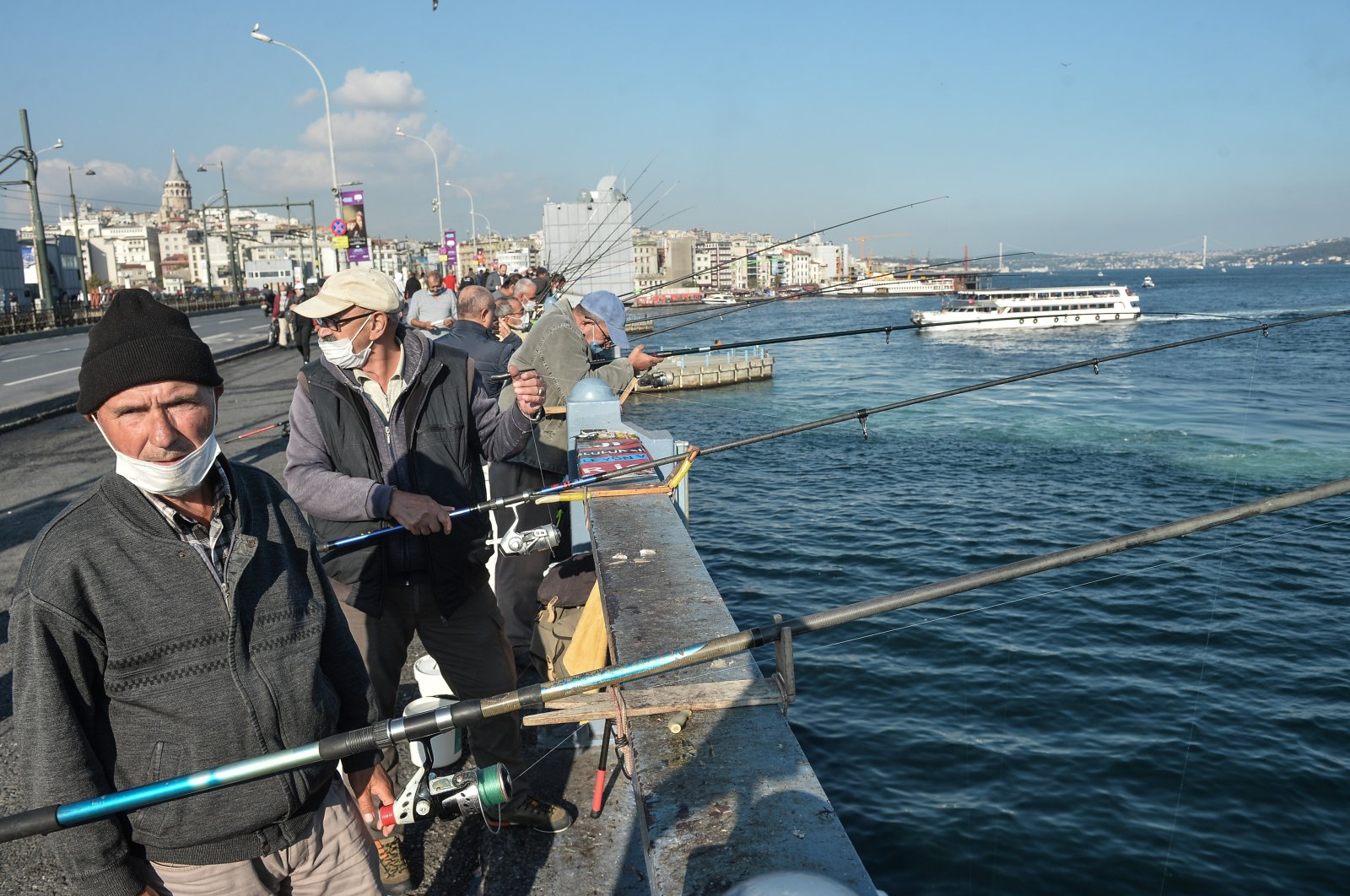 Fishermen cast their lines off Galata Bridge, some wearing masks to protect against COVID-19, in Istanbul, Turkey, Nov. 2, 2020. (DHA Photo)