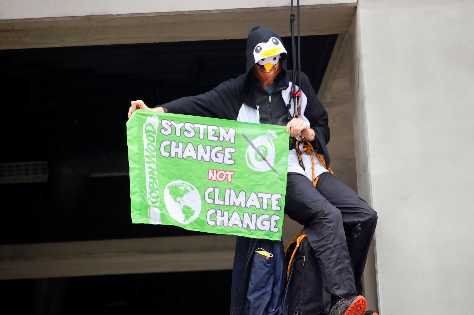 A climate activist holds a banner as he rappels from a roof during a protest against the official opening of the new Berlin-Brandenburg Airport (BER), in Schoenefeld, near Berlin, Germany, Oct. 31, 2020. (Reuters File Photo)