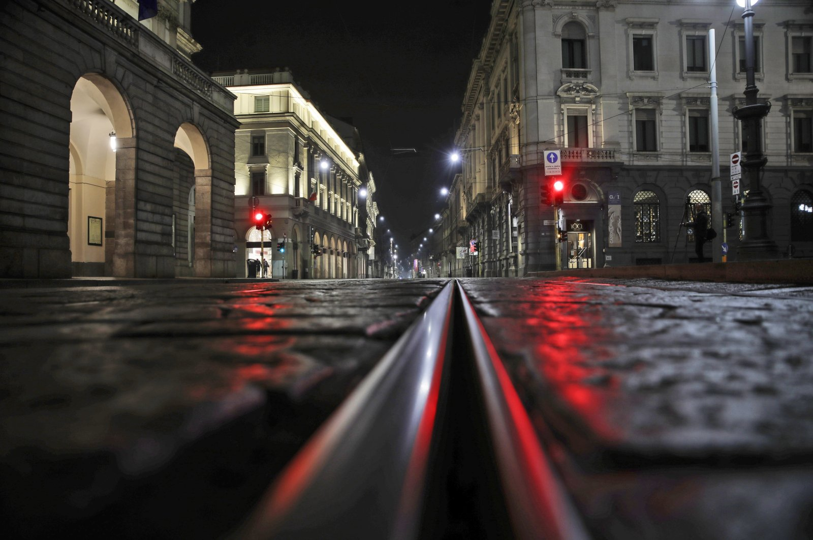 An empty street in front of La Scala opera house (L) is illuminated by a red traffic light in Milan, Italy, Oct. 25, 2020. (AP Photo)