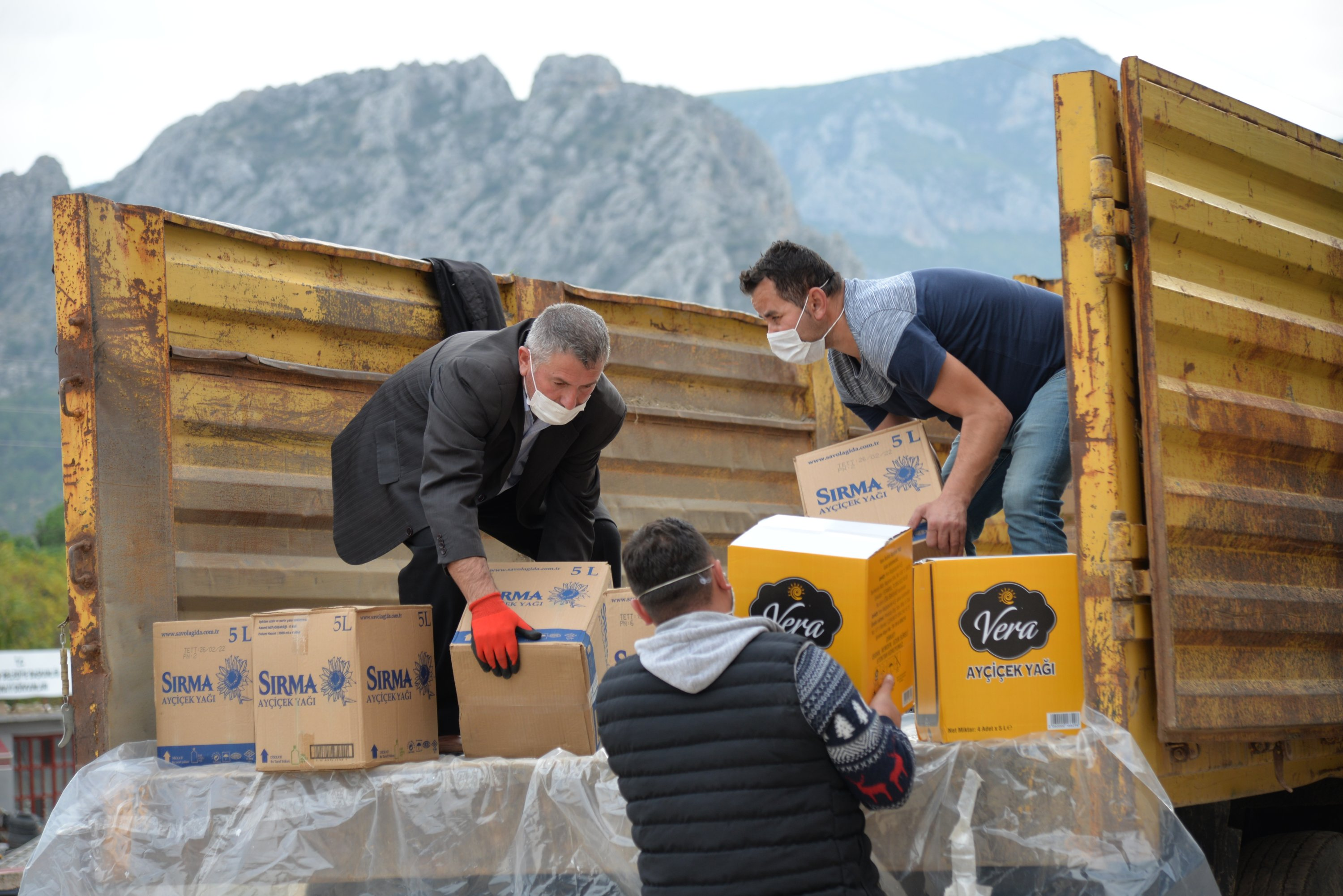Three men load aid packages sent by people in Bilecik's Inhisar district for earthquake survivors in Izmir, Turkey, Nov. 3, 2020. (AA Photo )
