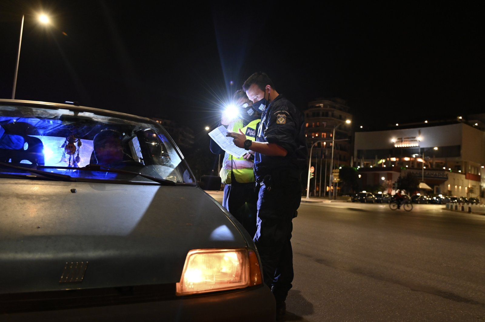 Police check the documents of a driver during the lockdown to contain the spread of COVID-19 in the northern city of Thessaloniki, Greece, Tuesday, Nov. 3, 2020. (AP Photo)