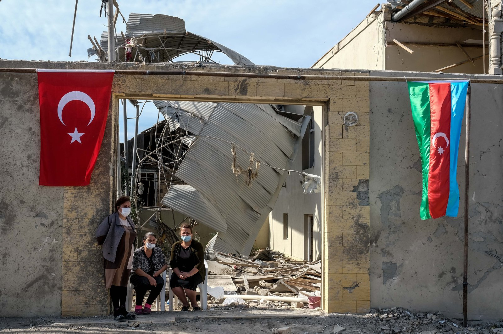 Locals in Ganja sit in front of a damaged house decorated with both Azerbaijani and Turkish flags, Azerbaijan, Oct. 21, 2020.