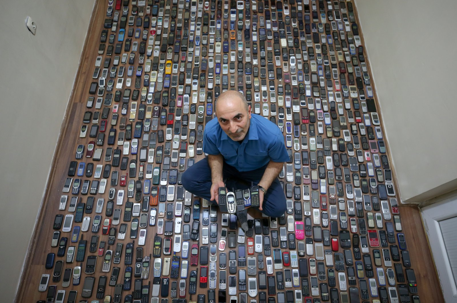 Şahabettin Özçelik poses with his phone collection, in Van, eastern Turkey, Nov. 5, 2020. (AA Photo)