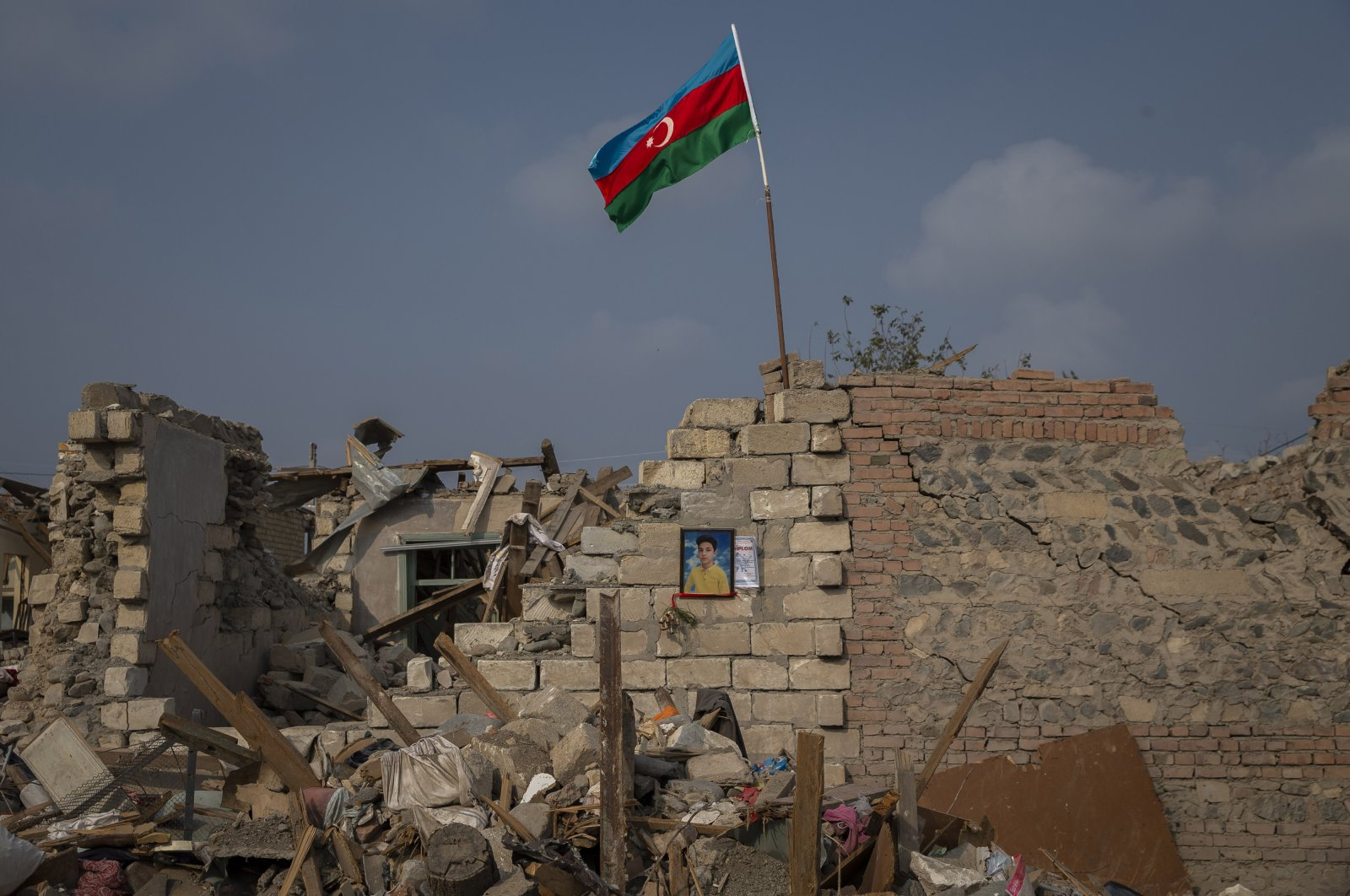 A picture of a boy killed in Armenian attacks hangs on the wall of a damaged building as an Azerbaijani flag waves on the rubble above, in the Azerbaijani city of Ganja, Nov. 5, 2020. (AA Photo)