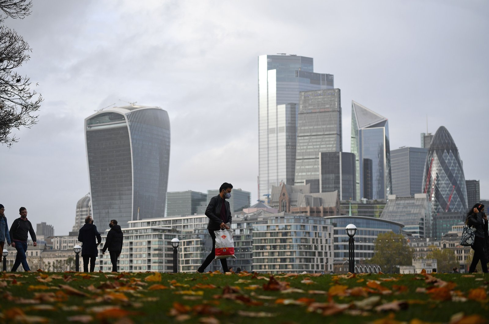 People walk along the southern bank of the River Thames with the office towers of the City of London in the background in London, U.K., Nov. 1, 2020. (AFP Photo)