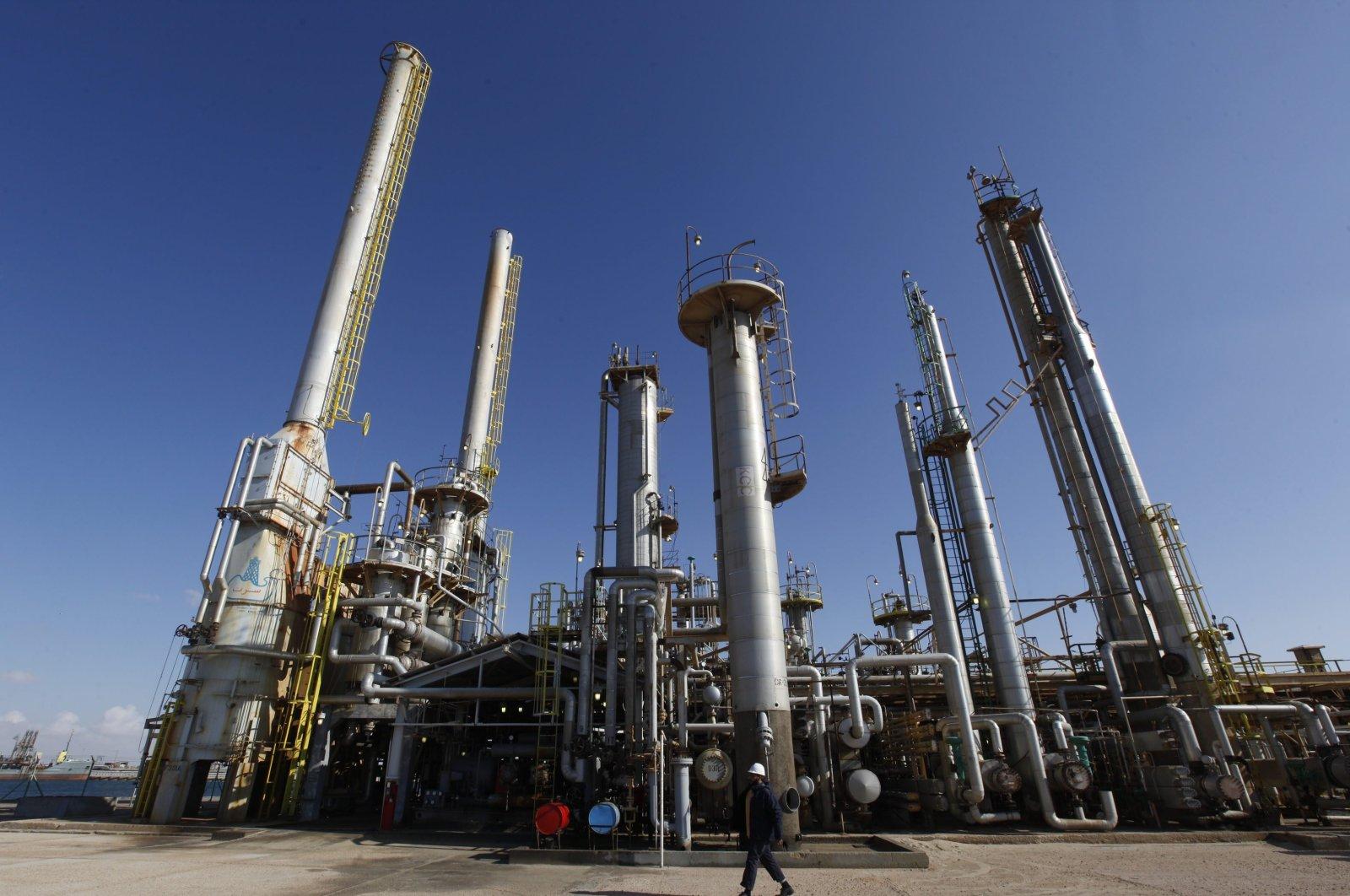 A Libyan oil worker walks in front of a refinery inside the Brega oil complex, in Brega, eastern Libya, Feb. 26, 2011. (AP Photo)