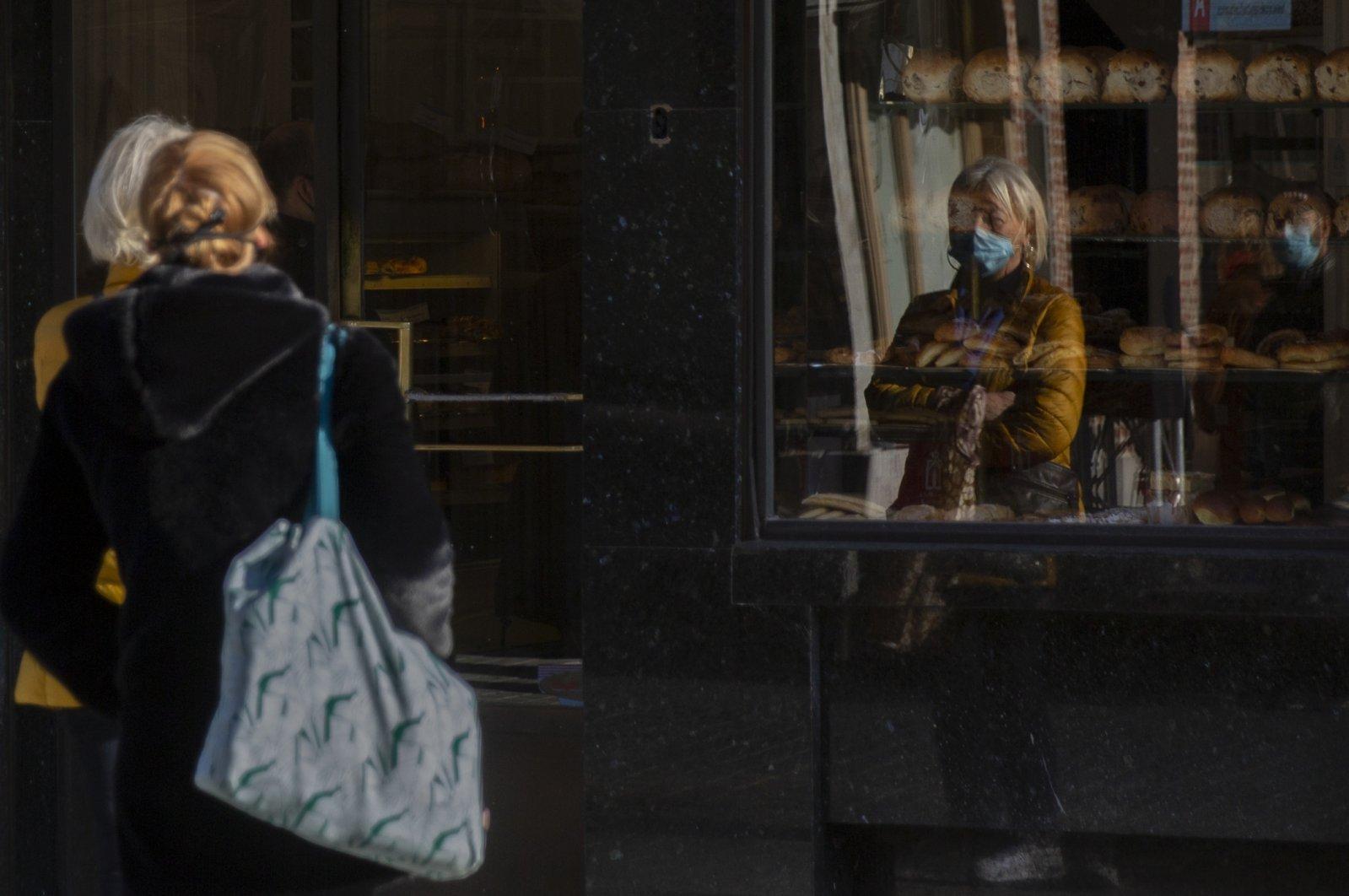 Two women wait in line at a bakery in Antwerp, Belgium, Nov. 4, 2020. (AP Photo)
