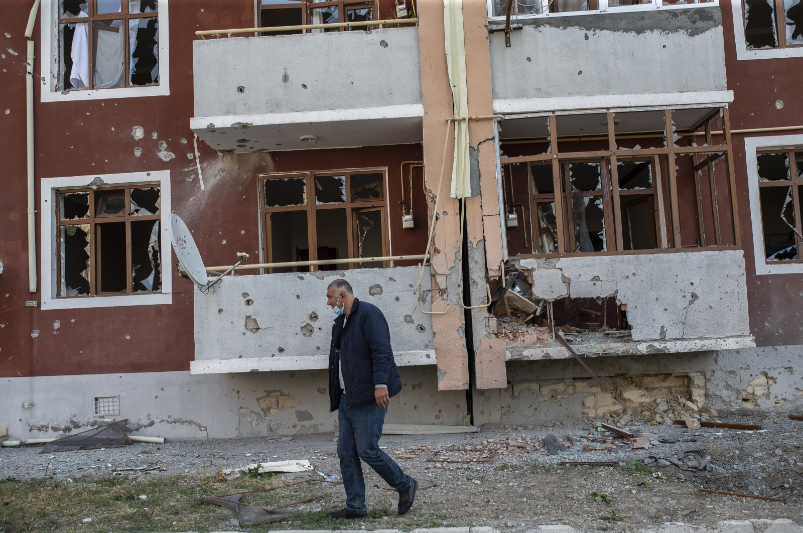 A man walks in front of a building damaged by Armenian shelling in the city of Tartar, Azerbaijan, Oct. 31, 2020. (AA Photo)