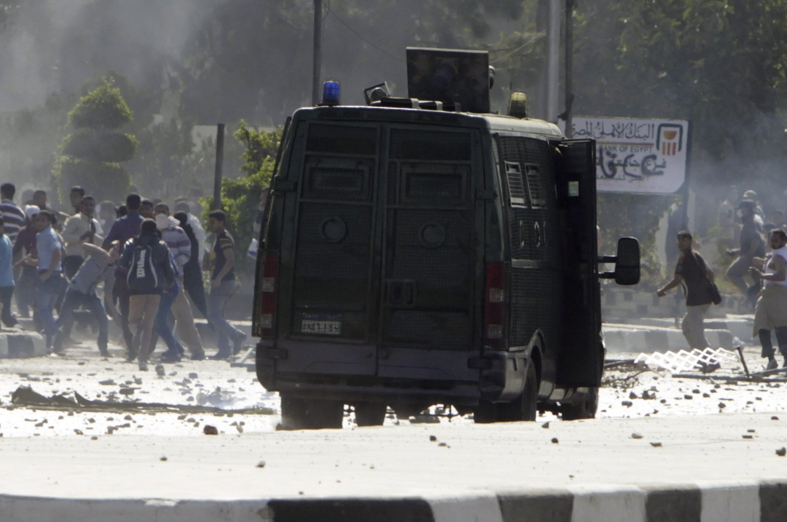 Protesters throw stones while running away from a riot police vehicle advancing toward them near Al-Azhar University in Cairo, Egypt, Oct. 20, 2013. (Reuters Photo)