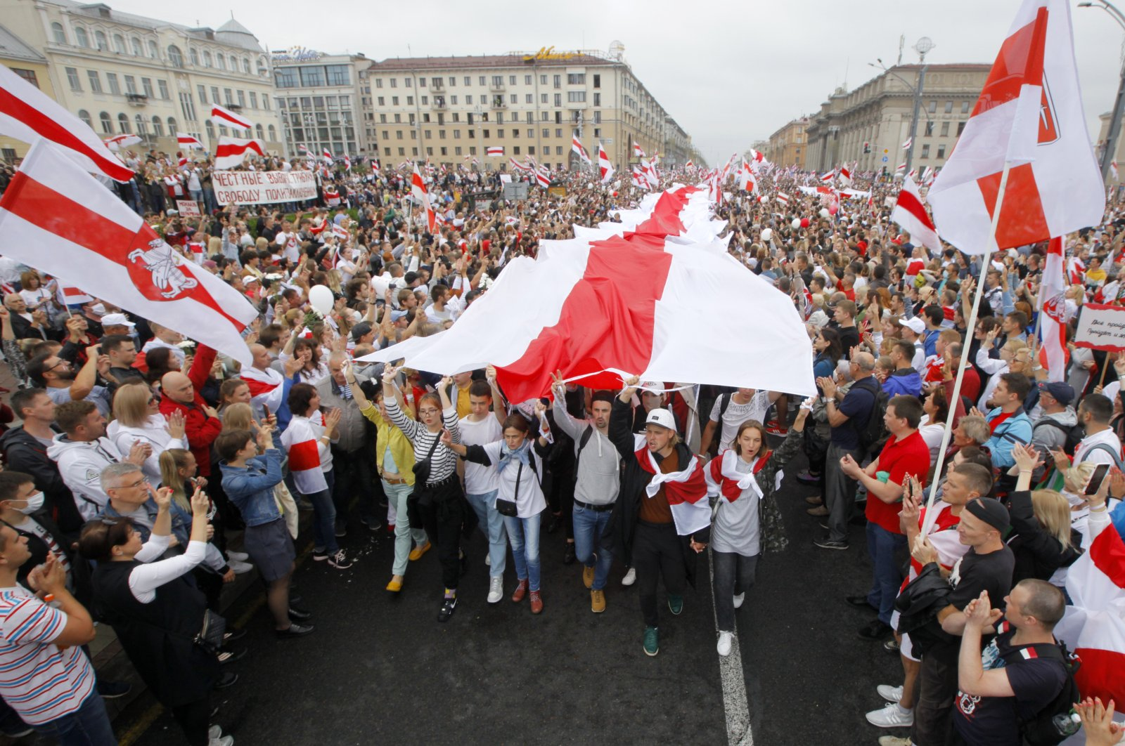 Demonstrators carry a huge historical flag of Belarus as thousands gather for a protest at the Independence Square in Minsk, Belarus, Aug. 23, 2020. (AP Photo)