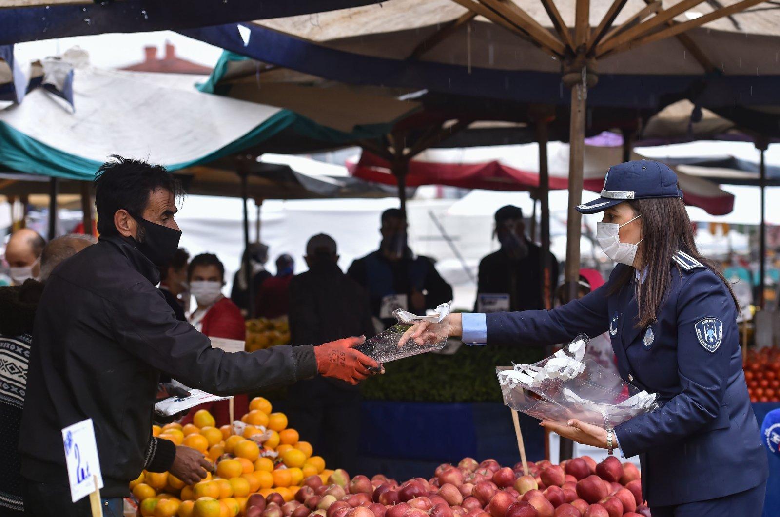 An Ankara municipal police officer hands a face shield to a fruit vendor at a market in the capital Ankara, Turkey, Nov. 3, 2020. (IHA Photo)
