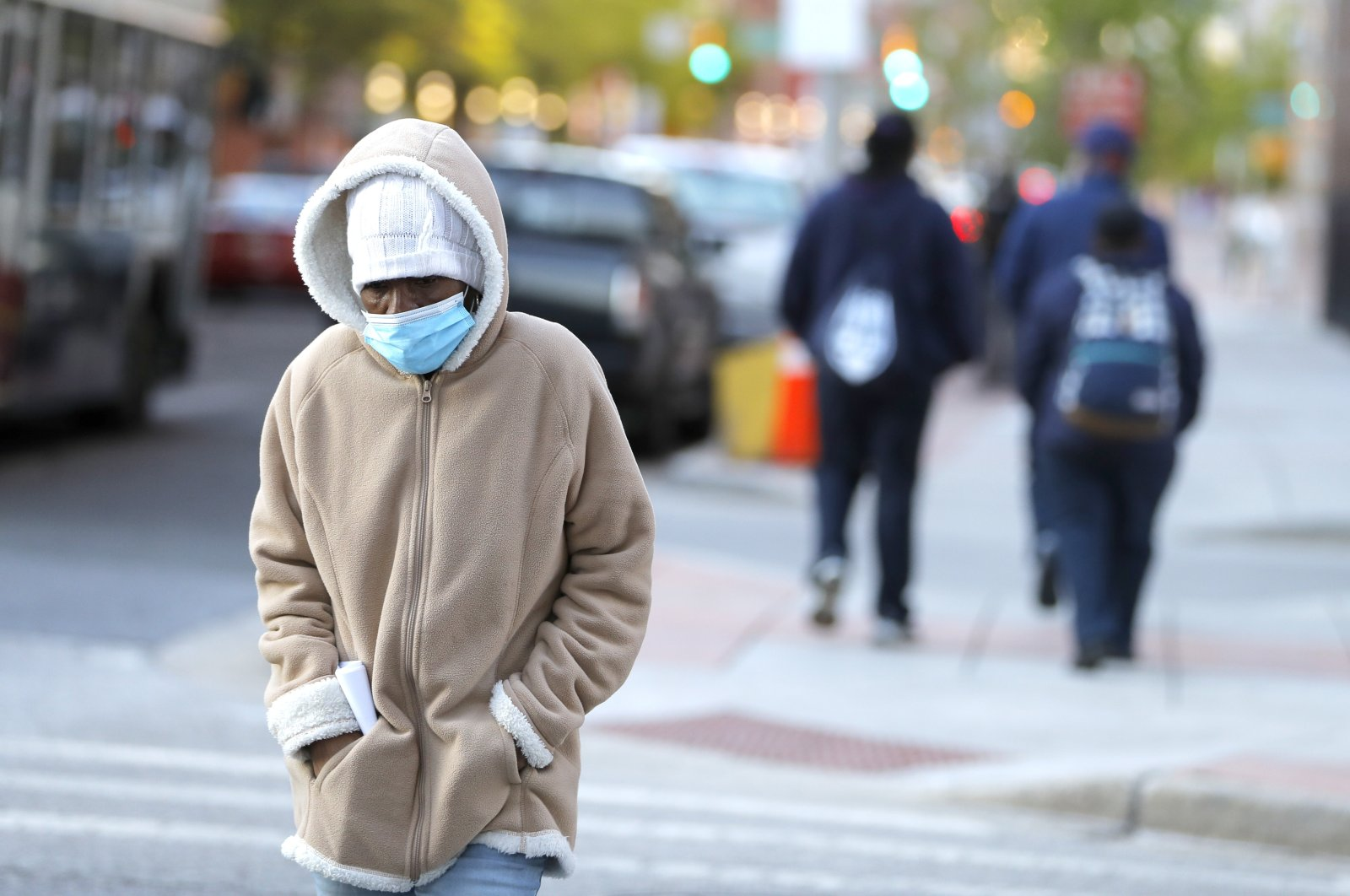 A person wears a face mask to protect from the coronavirus during a cold morning, Wednesday, April 22, 2020, in Baltimore. (AP Photo)
