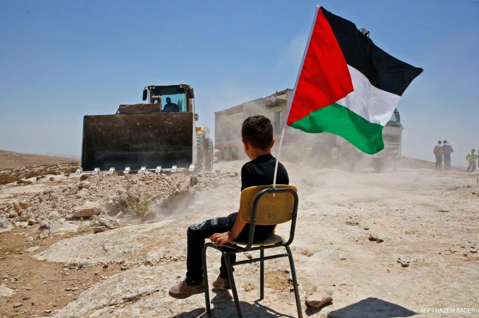 A Palestinian boy sits on a chair with a national flag as Israeli authorities demolish a school in the soon-to-be-relocated village of Yatta, south of the West Bank city of Hebron, July 11, 2018. (AFP File Photo)