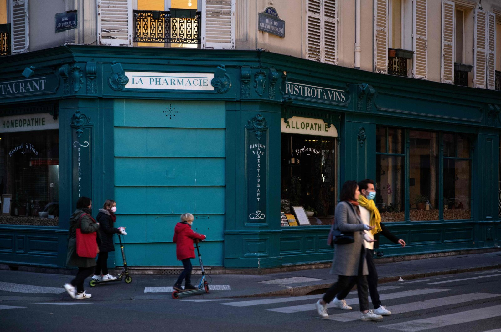 People wearing protective masks walk past closed a restaurant and pharmacy, Paris, Nov. 4, 2020. (AFP Photo)