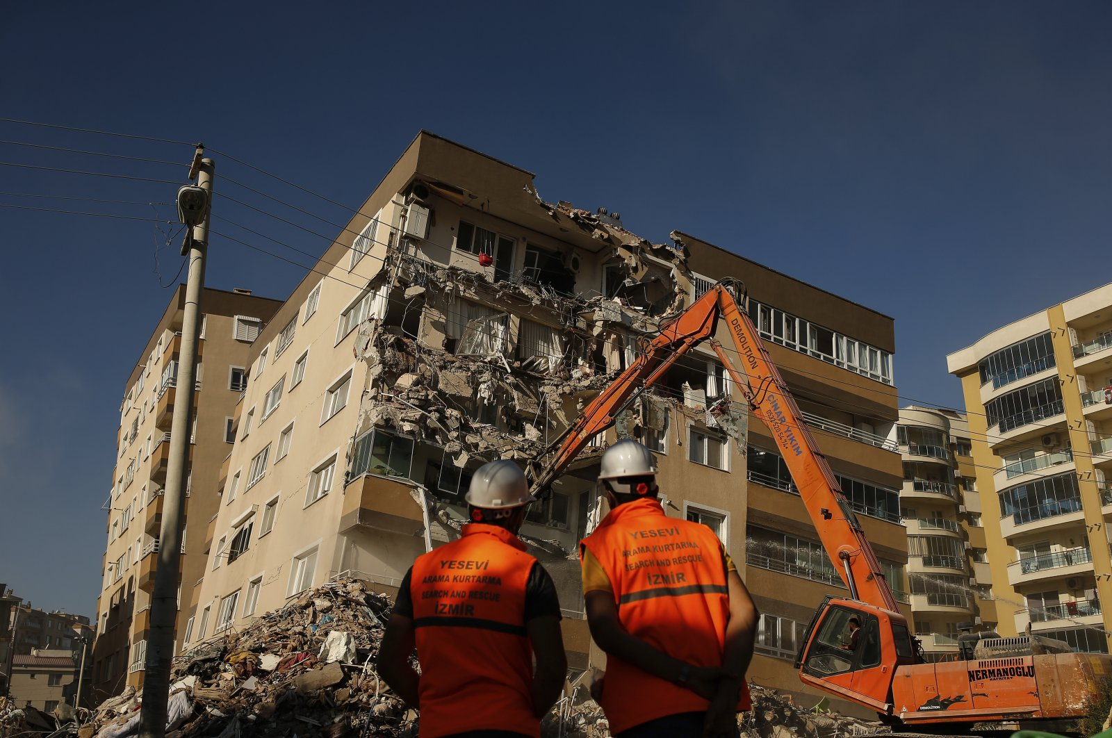 Workers watch as a bulldozer demolishes a damaged building in Izmir, western Turkey, Nov. 4, 2020. (AP Photo)