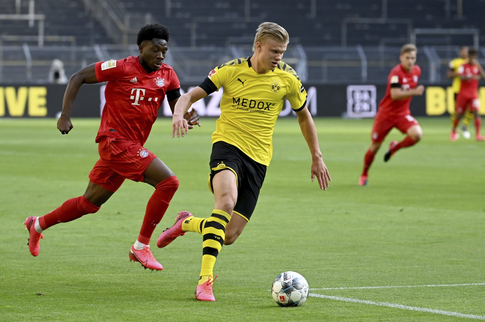 Bayern Munich's Alphonso Davies (L) challenges Dortmund's Erling Haaland for the ball during a Bundesliga match in Dortmund, Germany, May 26, 2020. (AP Photo)