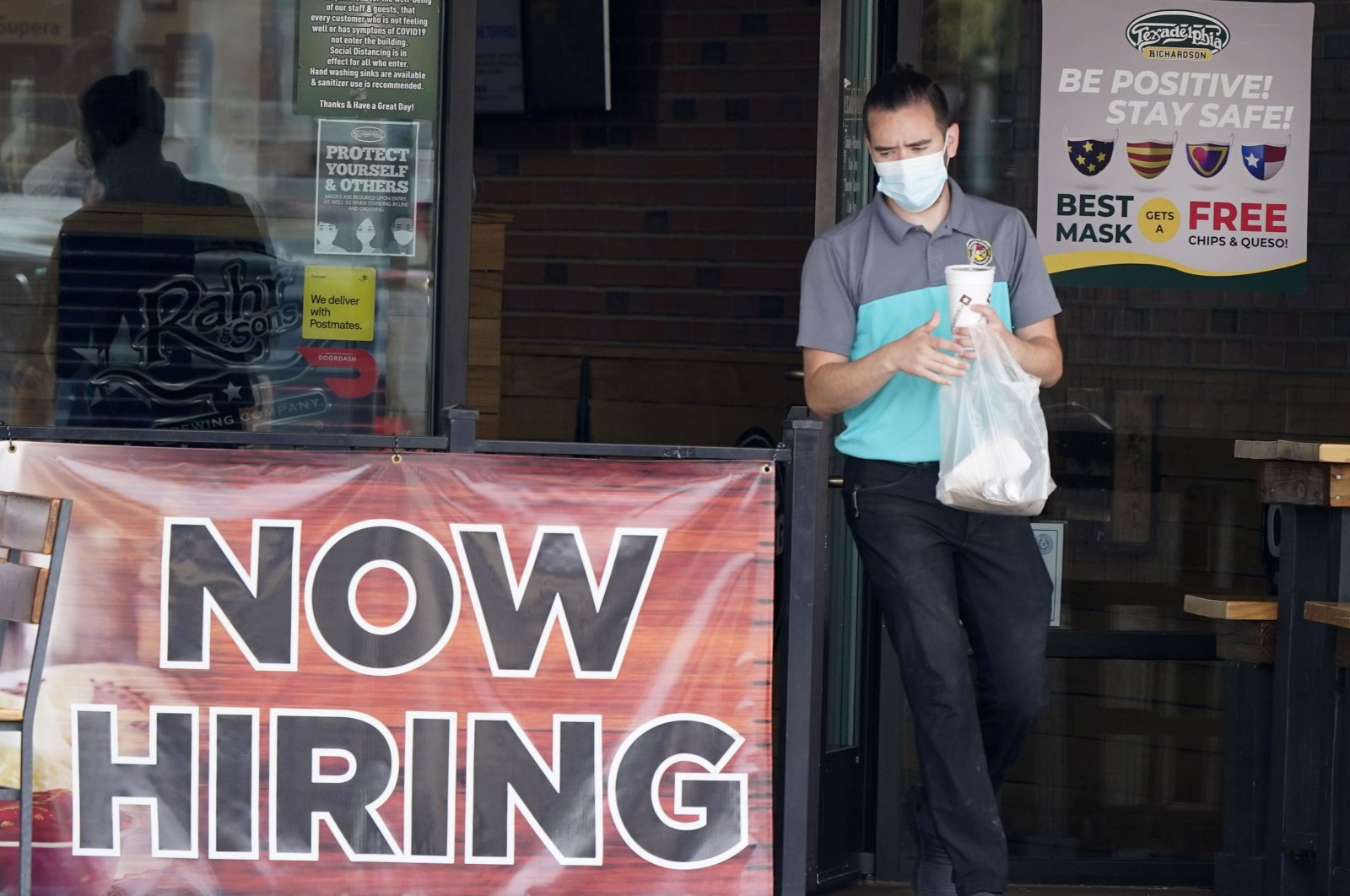 A customer wears a face mask as they carry their order past a now hiring sign at an eatery in Richardson, Texas, U.S., Sept. 2, 2020. (AP Photo)