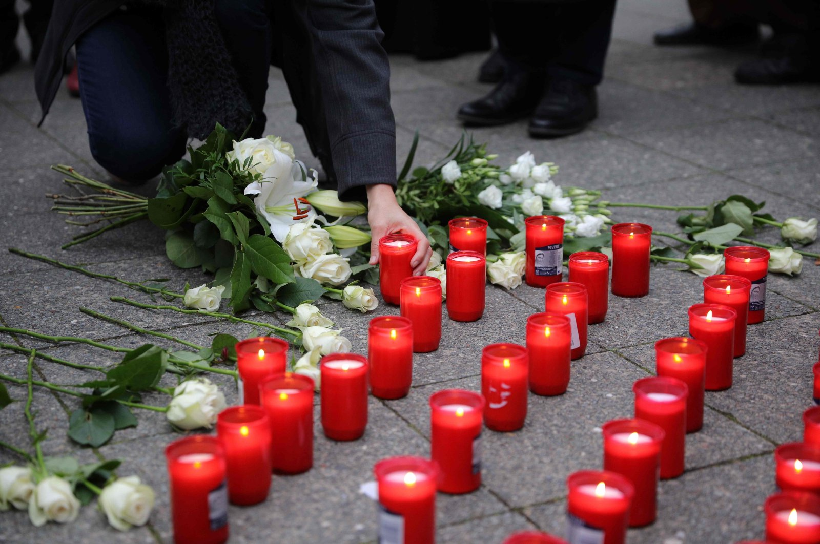 A man lights candles at a vigil remembering the victims of the terrorist attack in Vienna, outside the Austrian embassy in Berlin, Germany, on Nov. 6, 2020. (AFP Photo)