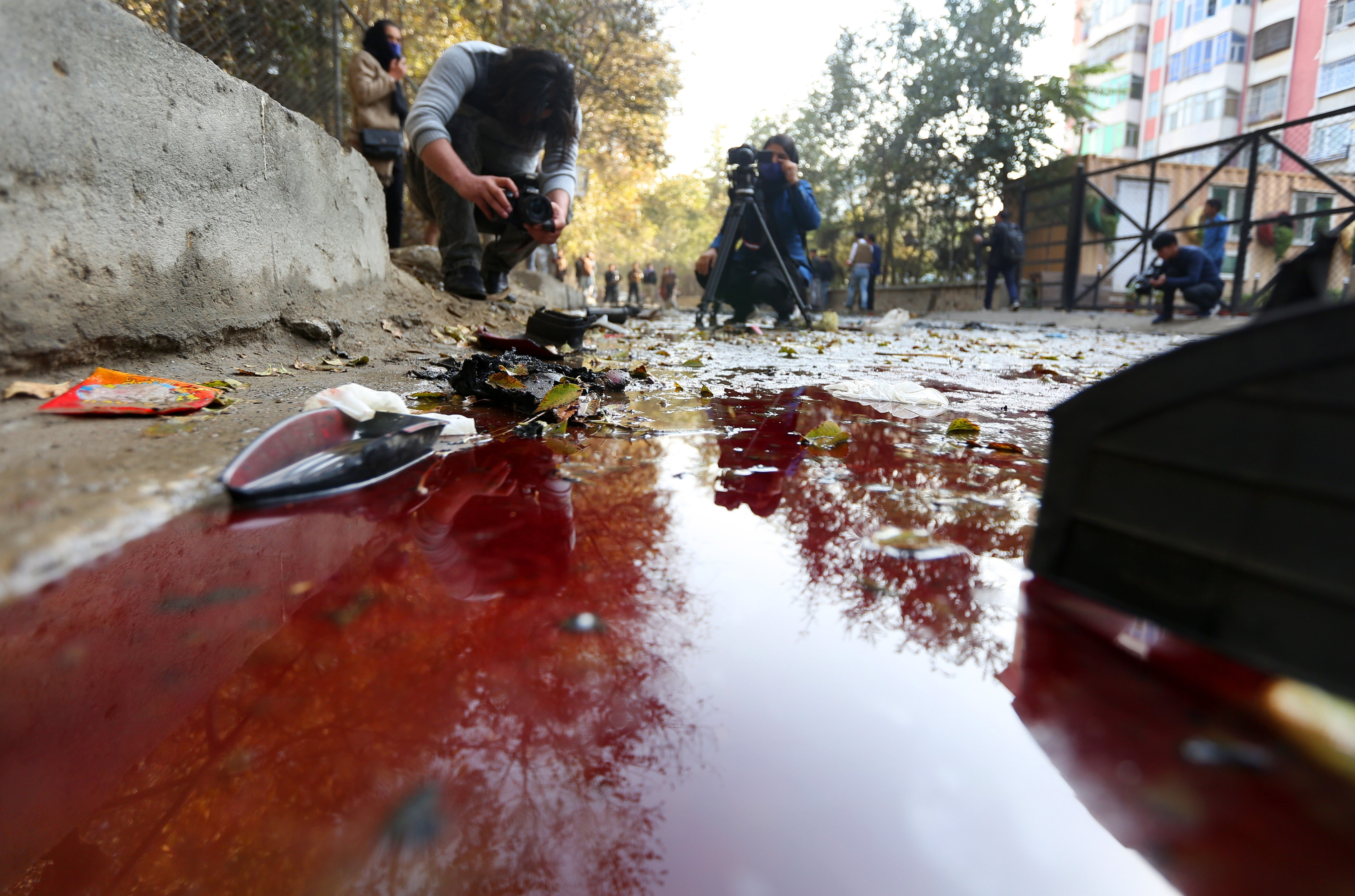 A journalist films blood on the ground at the scene of an explosion. According to local reports, three people, including former Afghan local TV journalist Yama Siawash, were killed in the blast, Kabul, Afghanistan, Nov. 7, 2020. (EPA Photo)