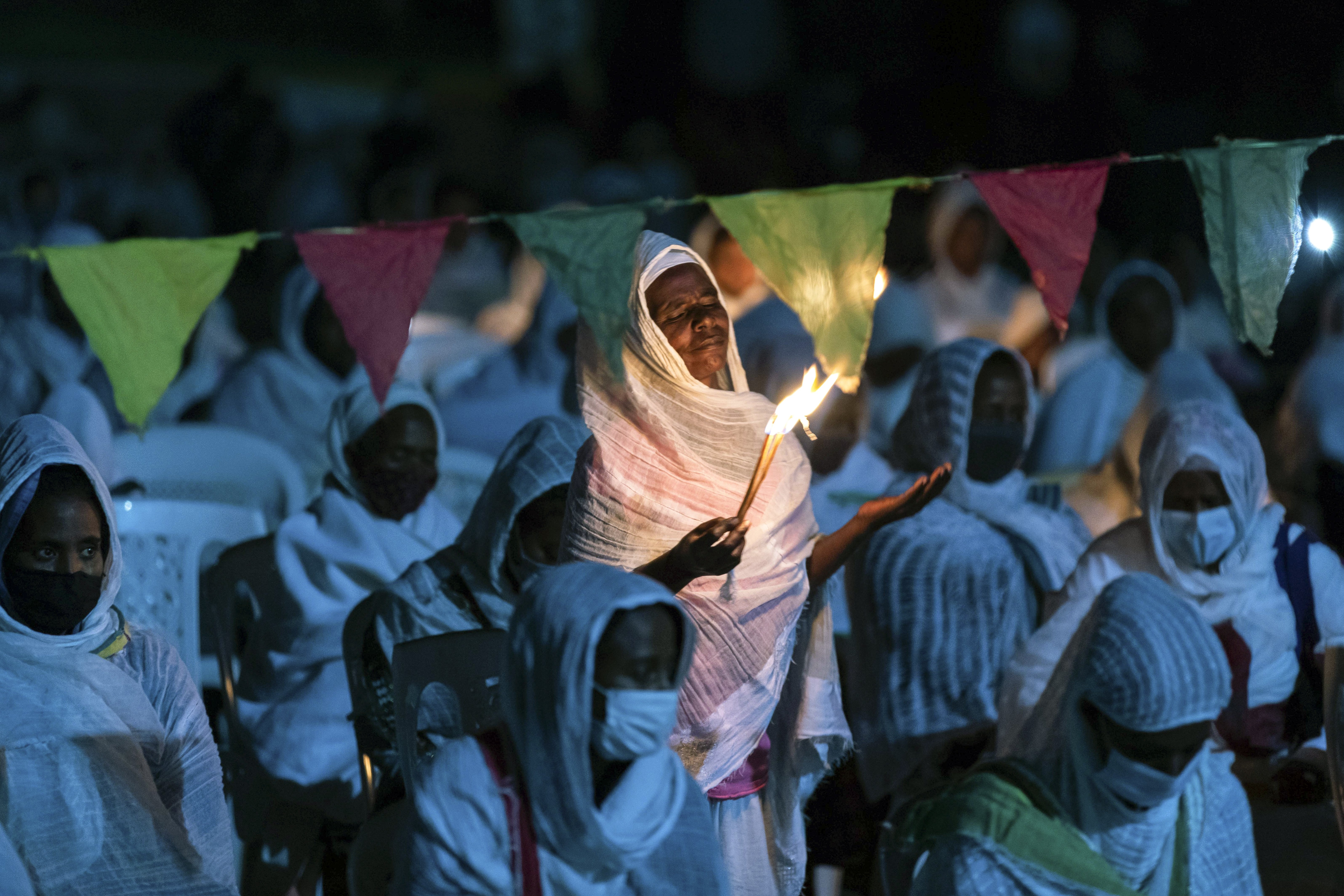 """Ethiopian Orthodox Christians light candles and pray for peace during a church service at the Medhane Alem Cathedral in the Bole Medhanealem area of the capital. Ethiopia's powerful Tigray region asserts that fighter jets have bombed locations around its capital, Mekele, aiming to force the region """"into submission,"""" while Ethiopia's army says it has been forced into an """"unexpected and aimless war,"""" Addis Ababa, Ethiopia, Nov. 5, 2020 (AP Photo/Mulugeta Ayene)"""