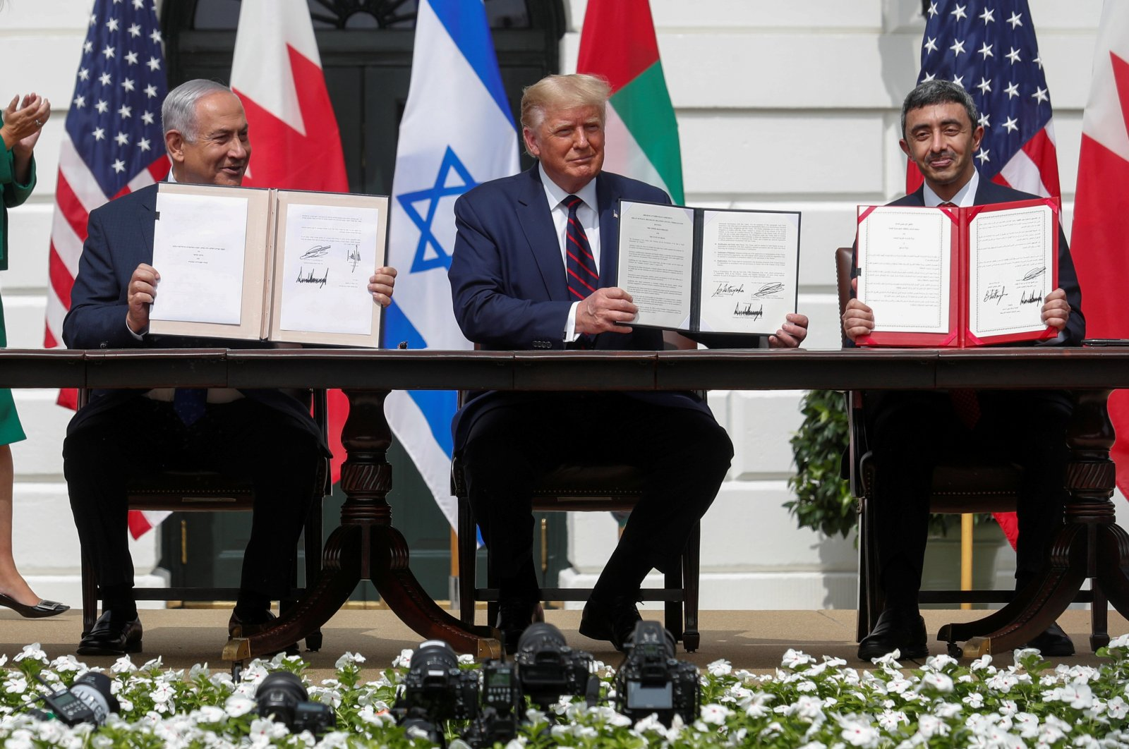 Israel's Prime Minister Benjamin Netanyahu, U.S. President Donald Trump and United Arab Emirates (UAE) Foreign Minister Abdullah bin Zayed display their copies of signed agreements as they participate in the signing ceremony of the Abraham Accords in Washington D.C., Sept. 15, 2020. (Reuters Photo)