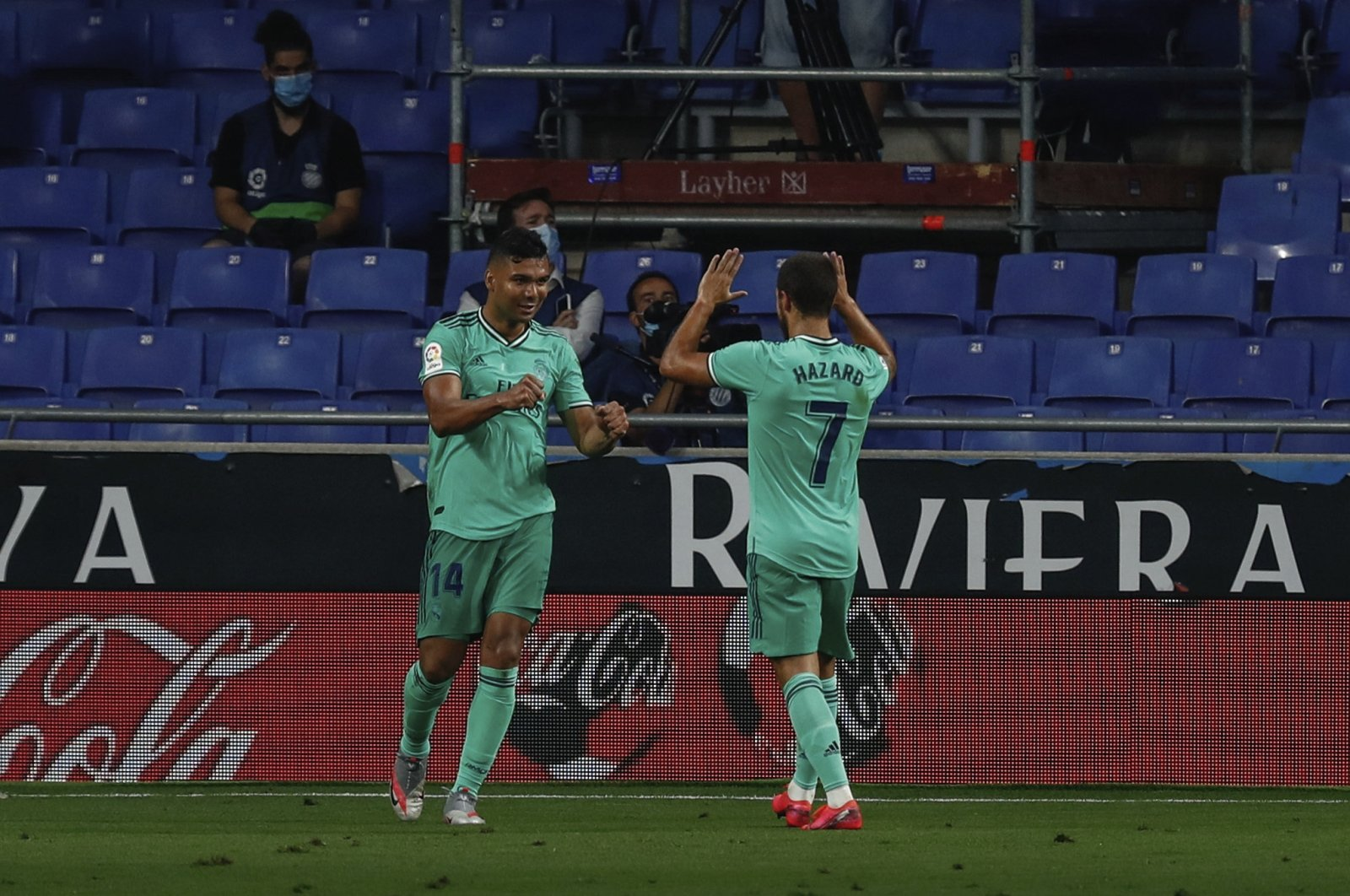 Real Madrid's Casemiro (L) is congratulated by teammate Eden Hazard after scoring the opening goal during the Spanish La Liga football match between RCD Espanyol and Real Madrid at the Cornella-El Prat stadium in Barcelona, Spain, June 28, 2020. (AP Photo)
