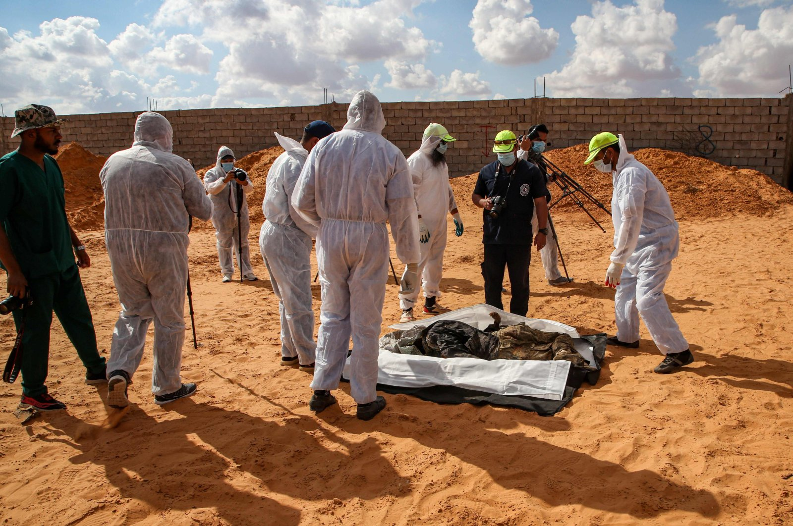 """Members of the public body leading the """"Search and Identification of the Missing,"""" backed by the U.N.-recognised Government of National Accord (GNA), gather around an unearthed body at a mass grave site in western Libya's Tarhuna region on Nov. 7, 2020."""
