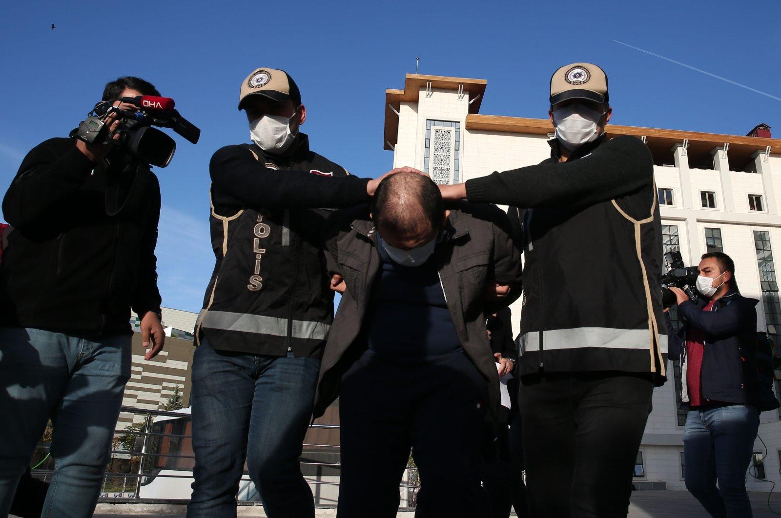 Police officers escort FETÖ suspect K. Y. M. following his capture, in Ankara, on Nov. 7, 2020. (AA Photo)