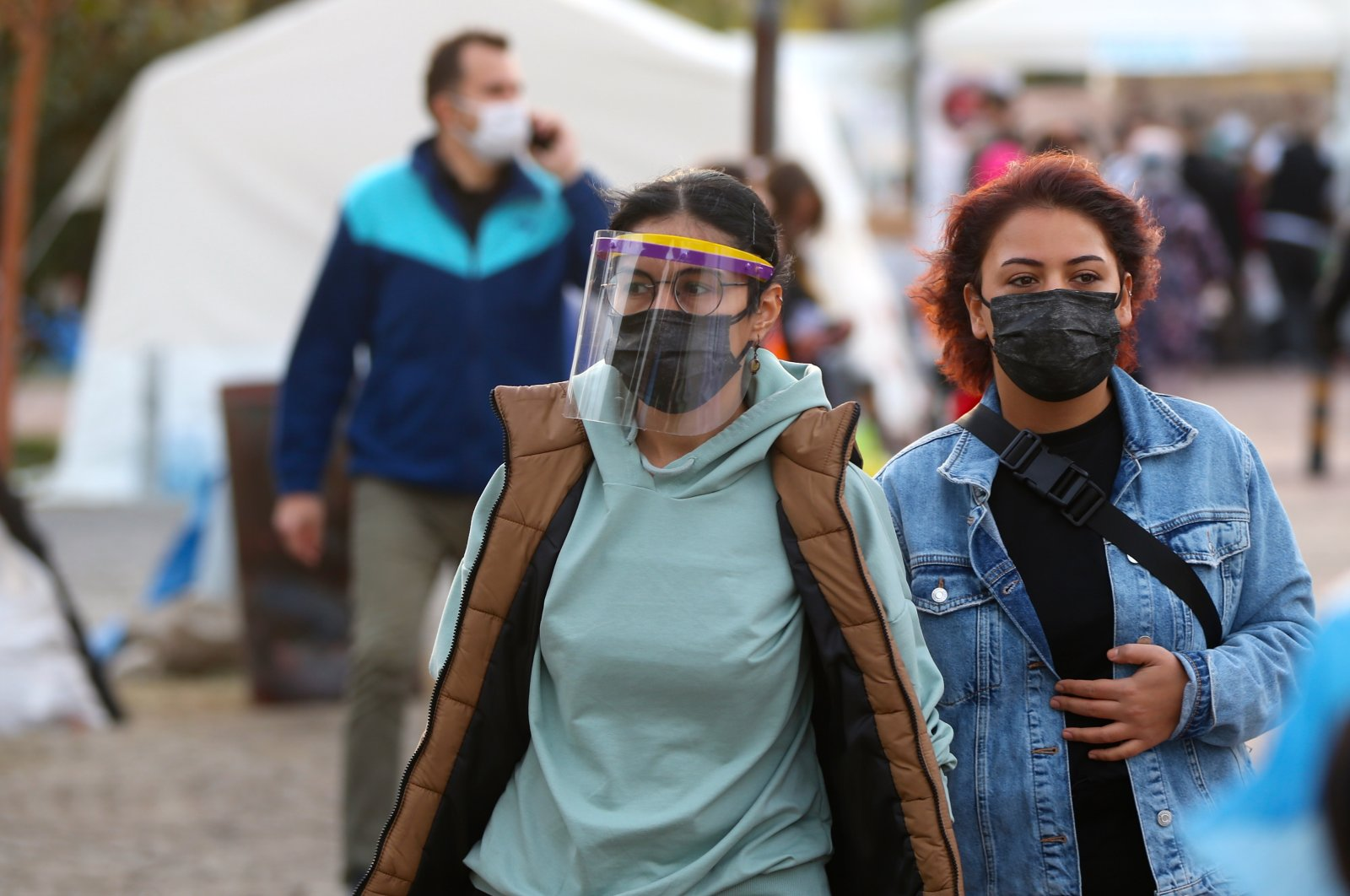 Two young women donning face masks and shields walk at a tent city in the western city of Izmir, which was hit by an earthquake on Oct. 30, 2020 killing 114 people and injured hundreds more, leaving thousands homeless or in search of more secure buildings, on Nov. 7, 2020. (AA Photo)