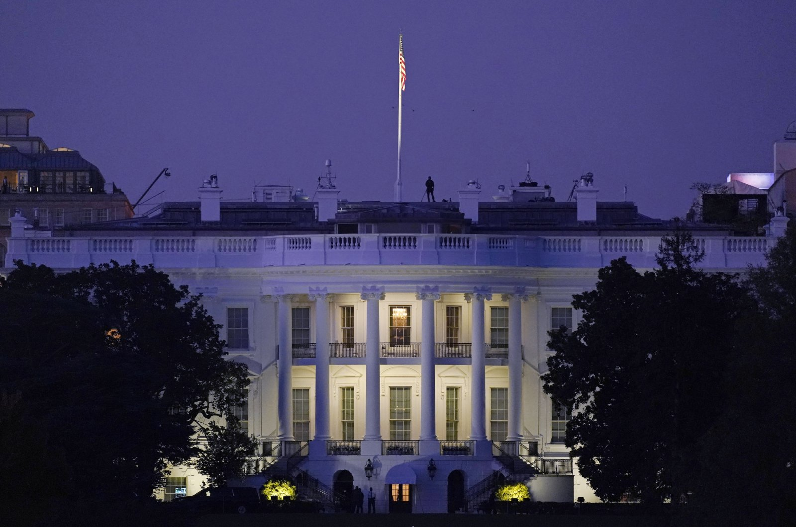 Lights shine from inside the White House as the sun sets, in Washington, D.C., Nov. 7, 2020. (AP Photo)