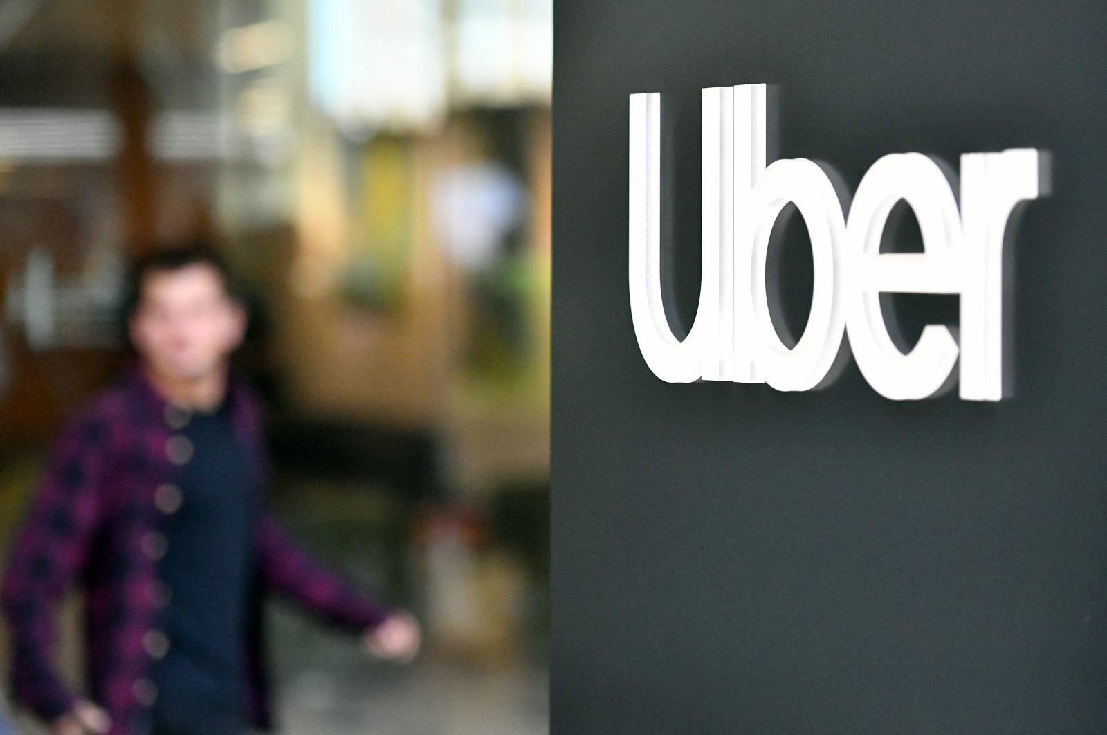 An Uber logo is seen on a sign outside the company's headquarters as people protest nearby in San Francisco, California, May 8, 2019. (AFP Photo)