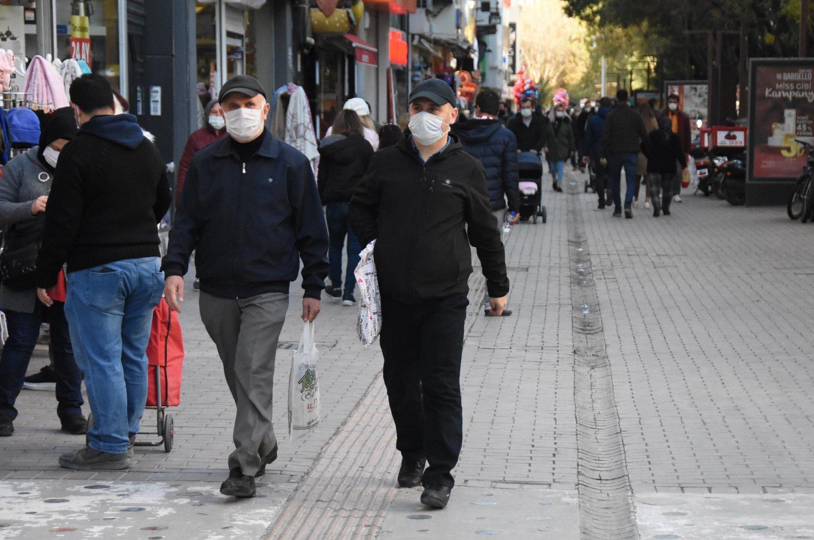 People wearing protective masks against COVID-19 walk on a street, Eskişehir, central Turkey, Nov. 7, 2020. (DHA Photo)