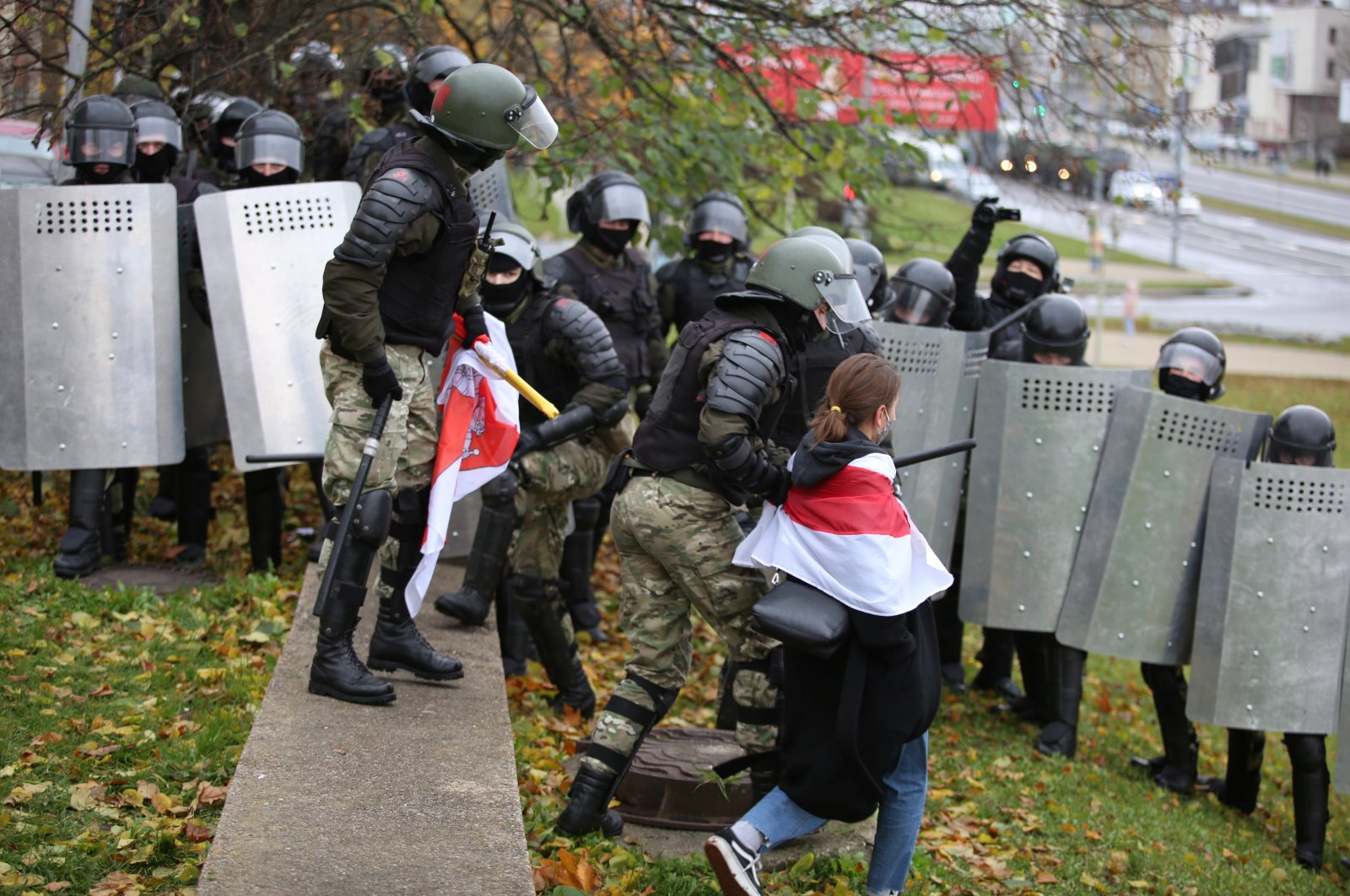 A woman wearing a historical white-red-white flag of Belarus is taken away by a law enforcement officer, Minsk, Nov. 8, 2020. (REUTERS Photo)