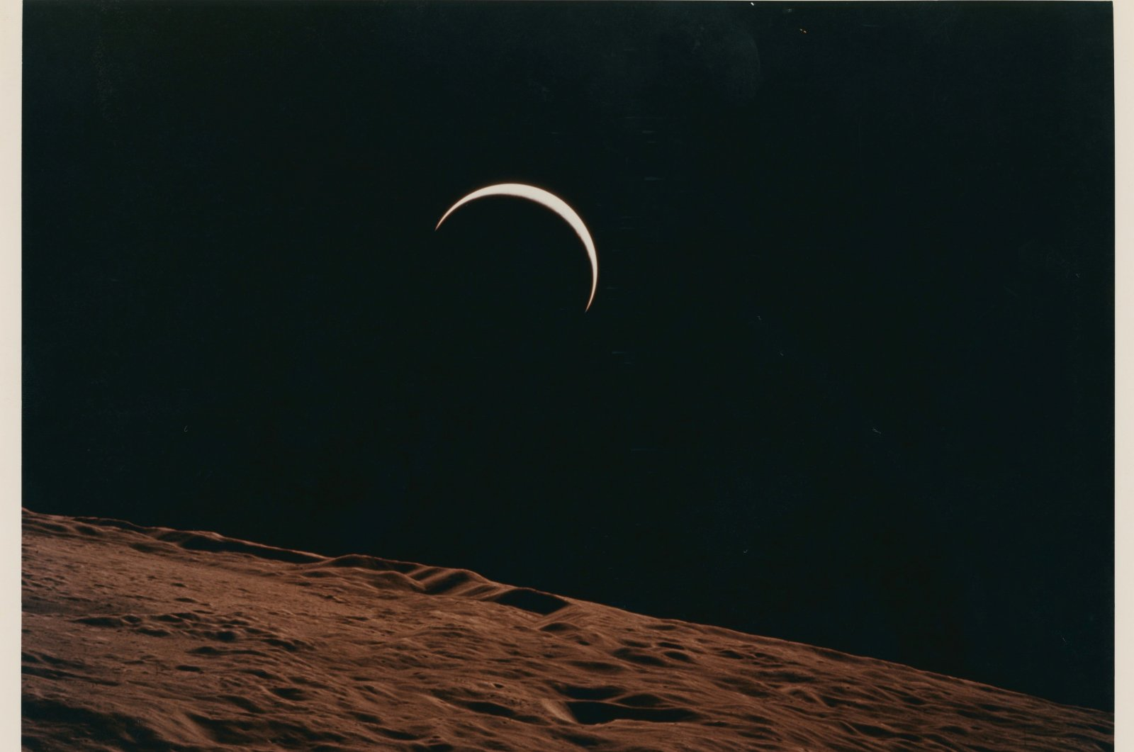 A handout image of Lot 558, Crescent Earth rising beyond the Moon's barren horizon, July 26- August 7, 1971, taken by Apollo 15 crewmember Alfred Worden, one of the space photographs in a collection up for auction at Christie's. (Alfred Worden/Christie's/Handout via REUTERS)