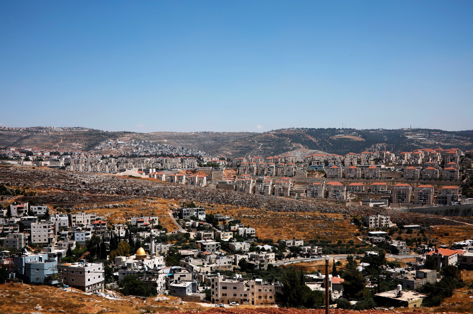 A general view shows Palestinian houses in the village of Wadi Fukin as the Israeli settlement of Beitar Illit is seen in the background in the occupied West Bank, June 19, 2019. (REUTERS Photo)
