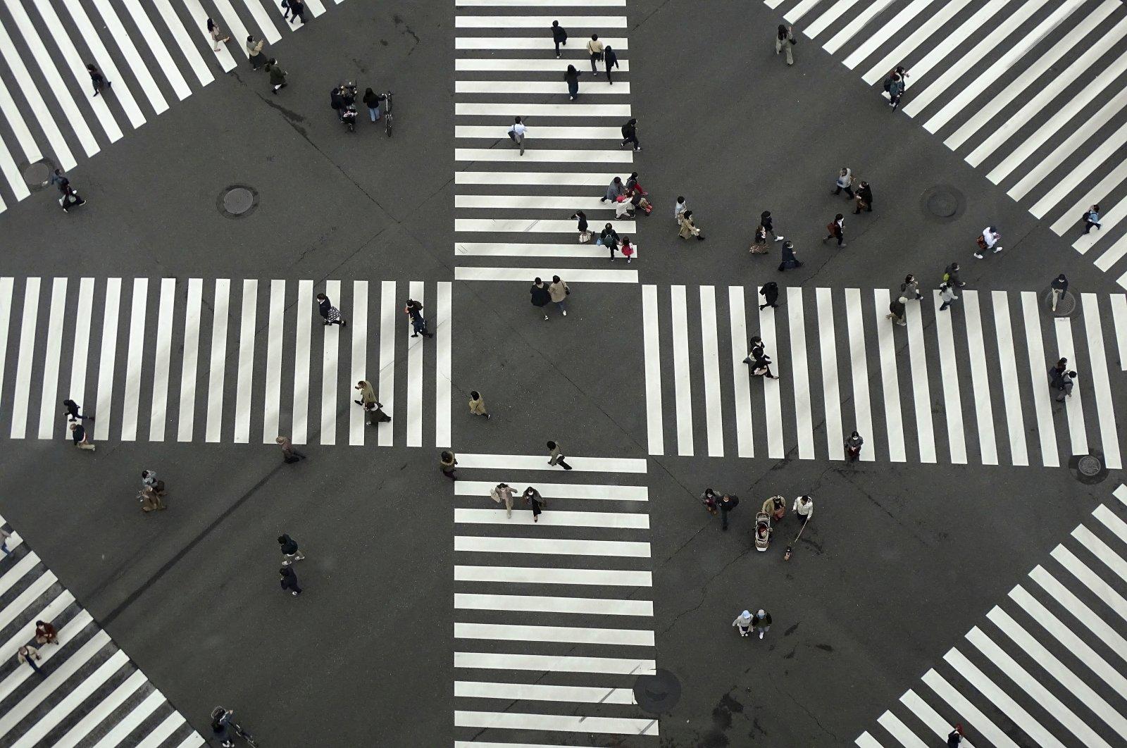 People walk across a pedestrian crossing along a shopping street, in Tokyo, Japan, Nov. 3, 2020. (AP Photo)
