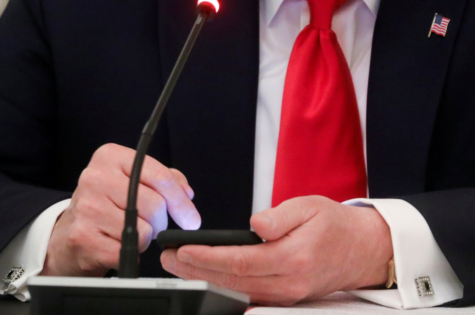 US President Donald Trump taps the screen on a mobile phone at the approximate time a tweet was released from his Twitter account, during a roundtable discussion on the reopening of small businesses in the State Dining Room at the White House in Washington, U.S., June 18, 2020. (Reuters Photo)