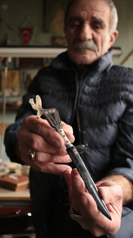 Mehmet Atışan shows an envelope opener he decorated at his workshop in Yalova, northwestern Turkey, Nov. 2, 2020. (AA PHOTO)