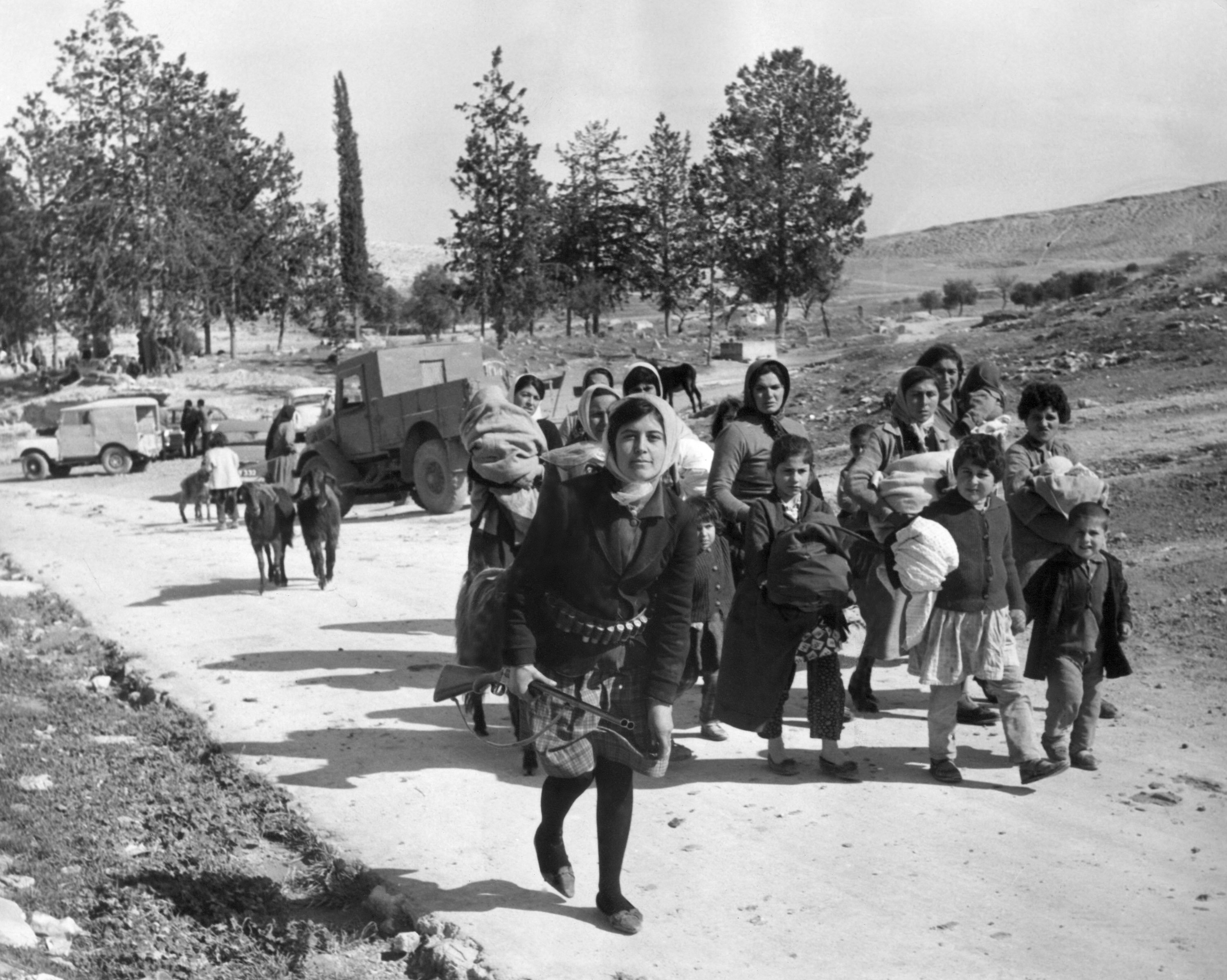 Armed with a double-barreled shotgun, a young Turkish Cypriot leads women and children from the village of Ayios Sozomenos to another nearby large Turkish village following a gun battle between Greeks and Turks on Feb. 6, 1964. About 100 women and children fled the village which had a total population of about 200 people, including 25 Greeks. (AP Photo)