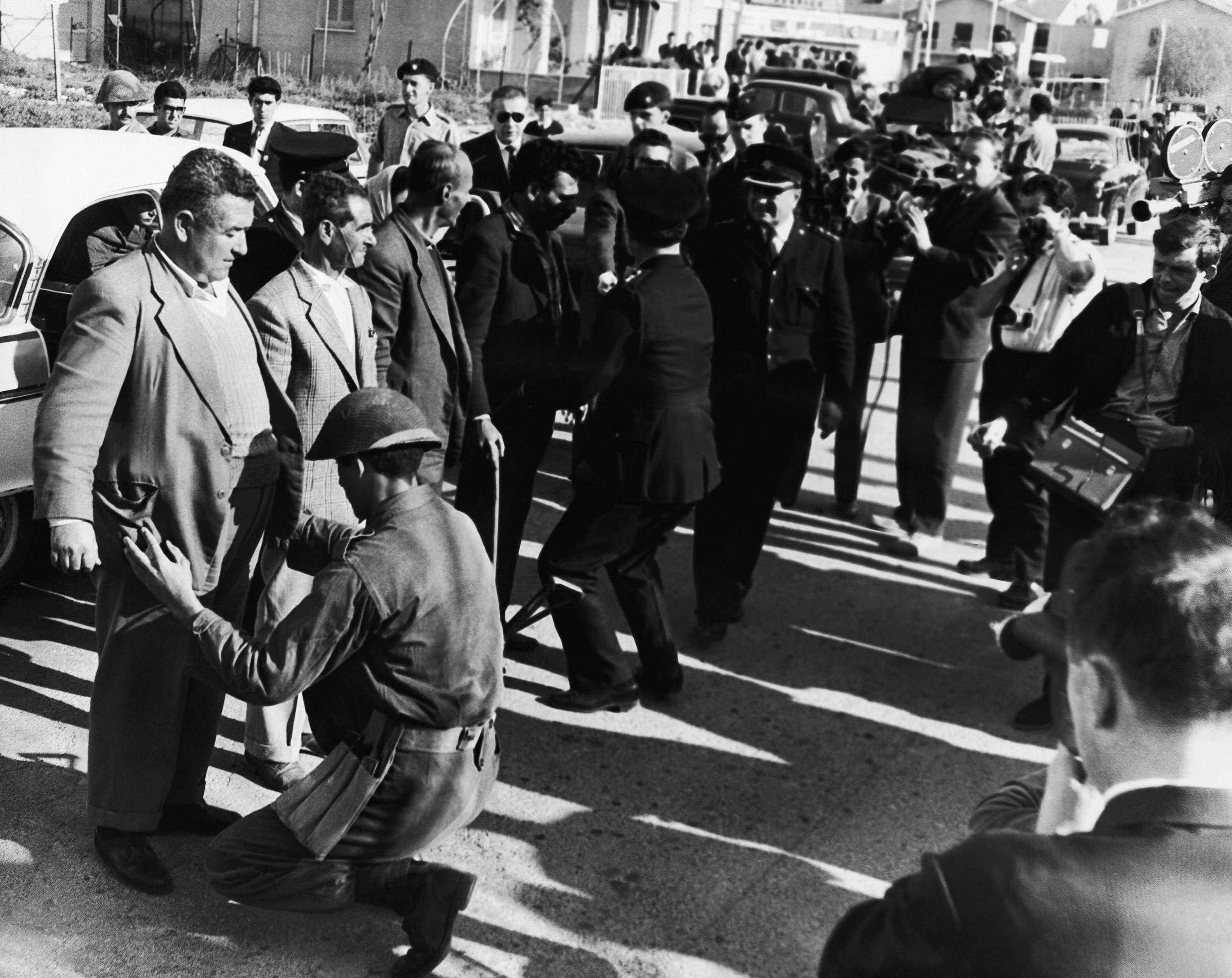 Greek police officers and a soldier search a party of Turkish Cypriots in Nicosia on March 13, 1964 before they left the city bound for Famagusta to bring back supplies by truck for Turkish Cypriots living in the Old Quarter of Nicosia. A British officer keeps watch during the routine search but is not seen in this picture. The Turks who make the daily journey to Famagusta are escorted by British soldiers in Ferret armored cars. (AP Photo)