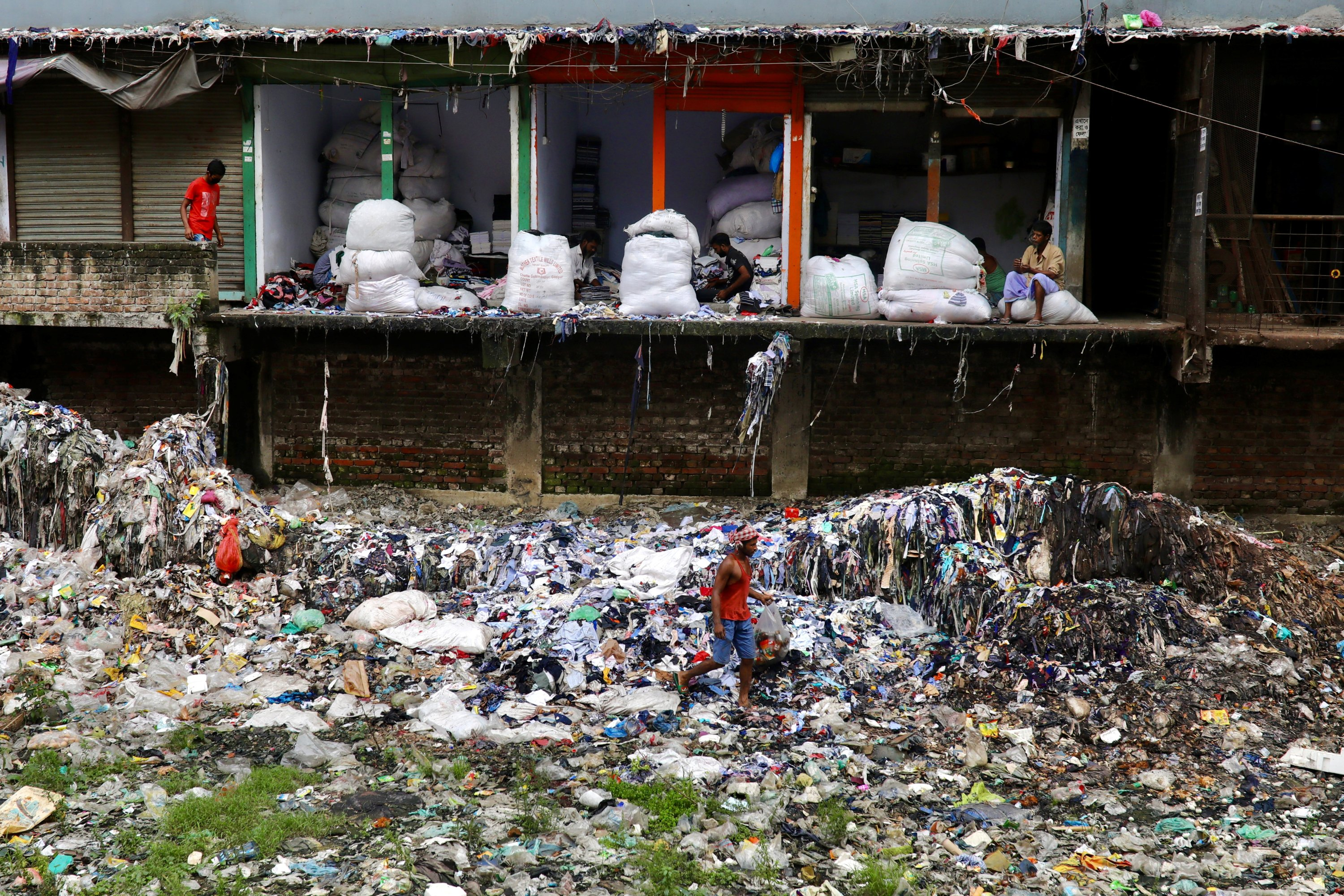 A man collects waste materials including plastics from the waste thrown by local garment companies in Dhaka, Bangladesh, October 18, 2020. REUTERS/Mohammad Ponir Hossain