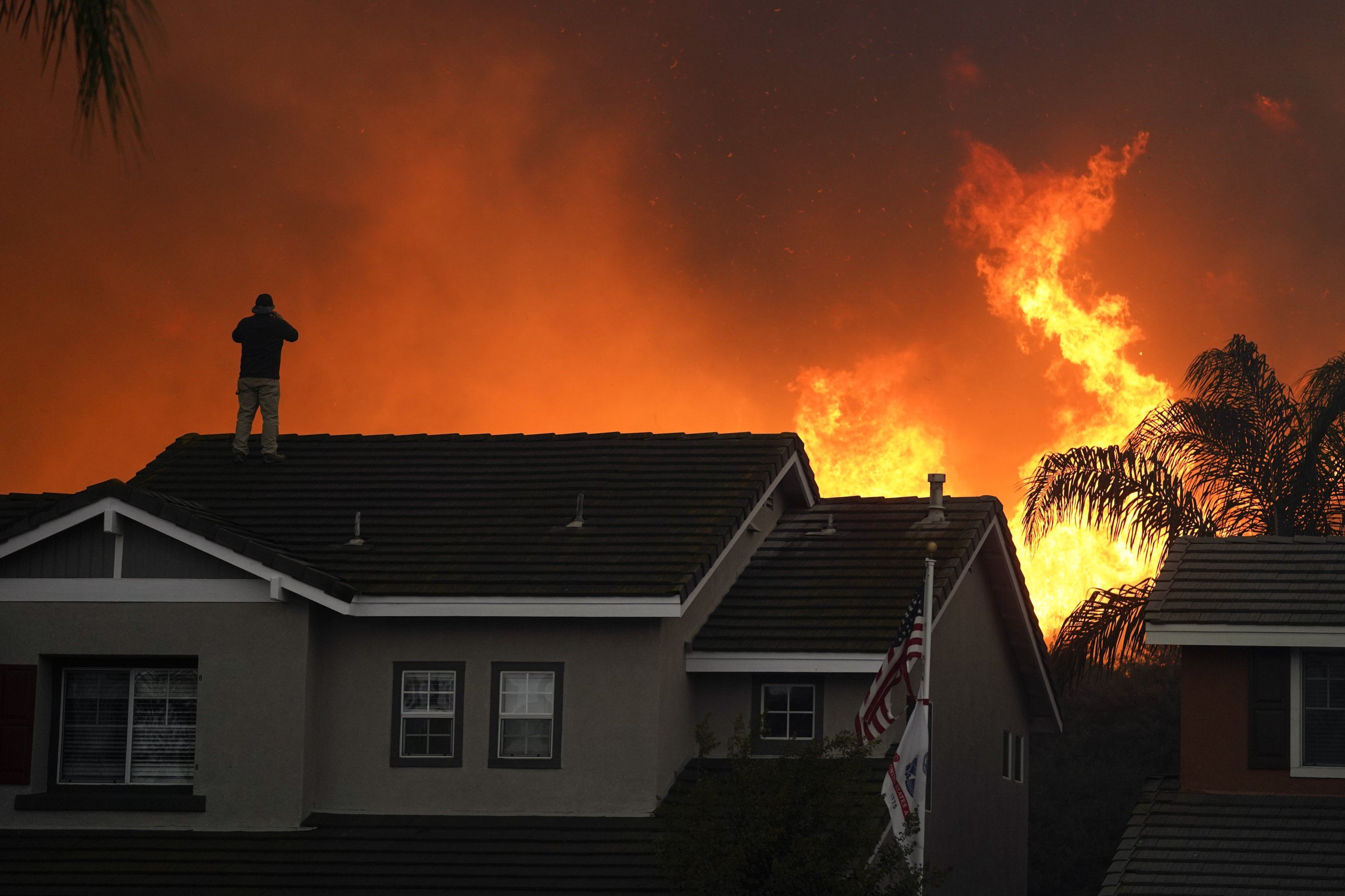 Herman Termeer, 54, stands on the roof of his home as the Blue Ridge Fire burns along the hillside Tuesday, Oct. 27, 2020, in Chino Hills, Calif. (AP Photo)