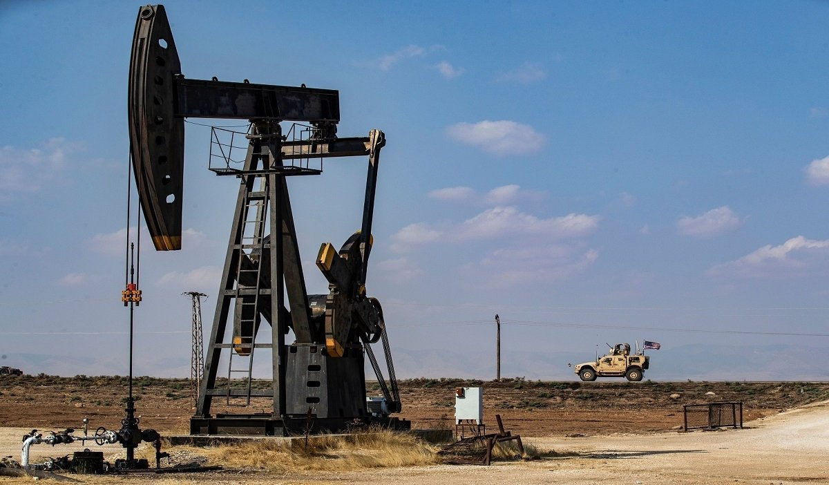 A U.S. military vehicle, part of a convoy arriving from northern Iraq, drives past an oil pump jack in the countryside of Syria's northeastern city of Qamishli on Oct. 26, 2019. (AFP via Getty Images)