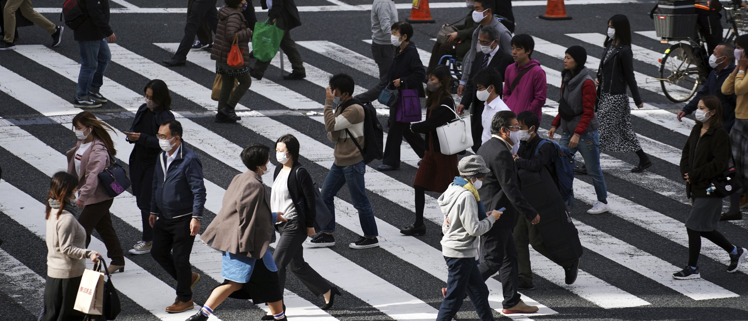 People wearing protective masks to help curb the spread of the coronavirus walk on a pedestrian crossing in Tokyo, Japan, Nov. 9, 2020. (AP Photo)