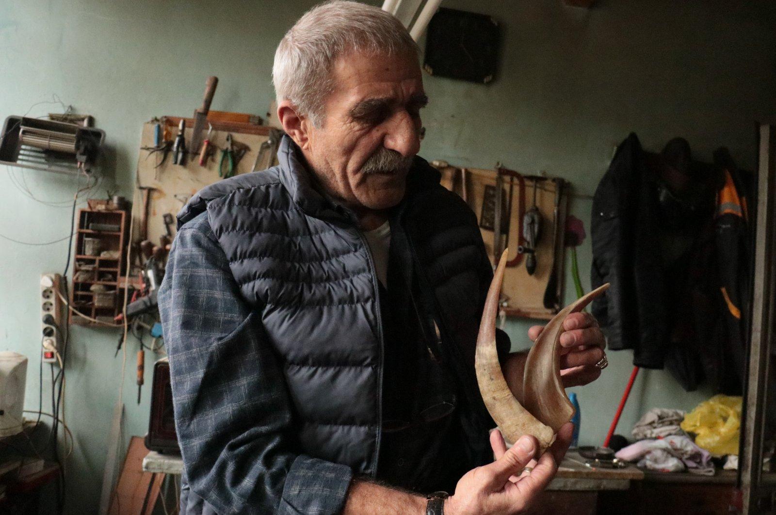 Mehmet Atışan holds a pair of horns at his workshop in Yalova, northwestern Turkey, Nov. 2, 2020. (AA PHOTO)